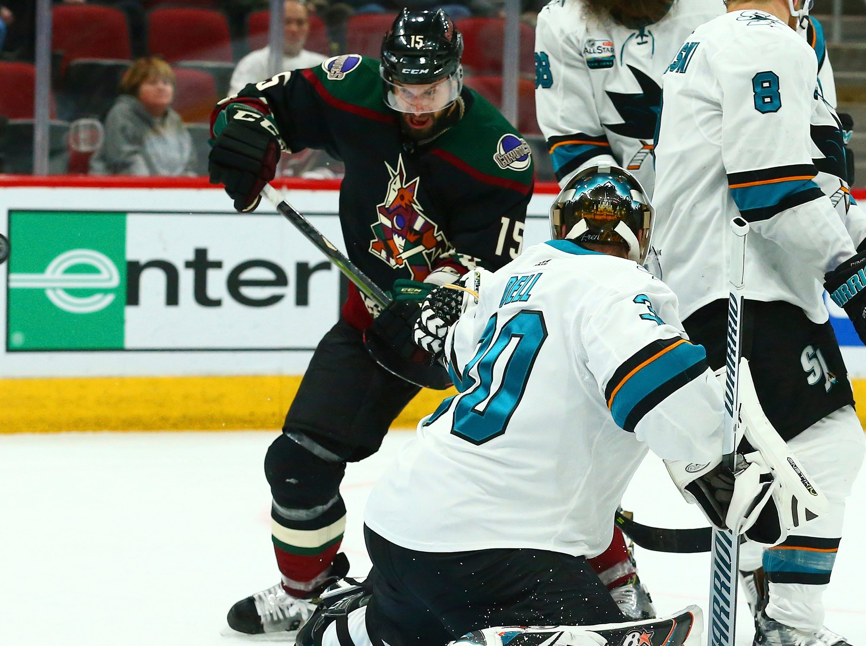 Arizona Coyotes center Brad Richardson (15) redirects the puck past San Jose Sharks goaltender Aaron Dell (30) for a goal during the second period of an NHL hockey game, Saturday, Dec. 8, 2018, in Phoenix. (AP Photo/Ross D. Franklin)