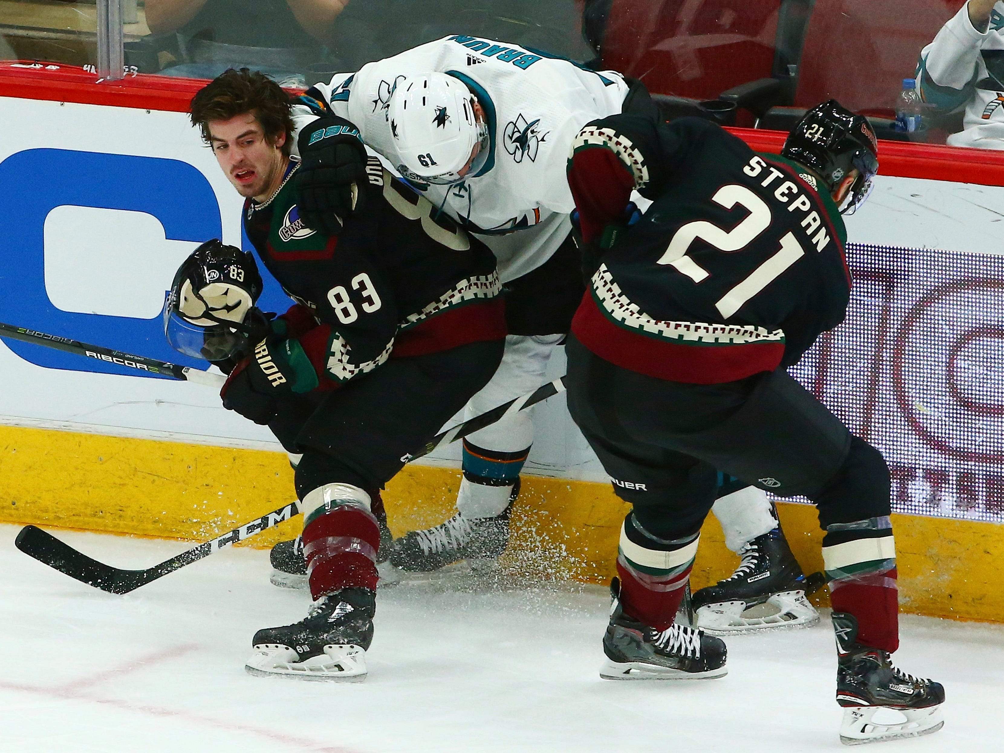Arizona Coyotes right wing Conor Garland (83) loses his helmet as San Jose Sharks defenseman Justin Braun (61) and Coyotes center Derek Stepan (21) battle for the puck during the third period of an NHL hockey game, Saturday, Dec. 8, 2018, in Phoenix. The Sharks defeated the Coyotes 5-3.