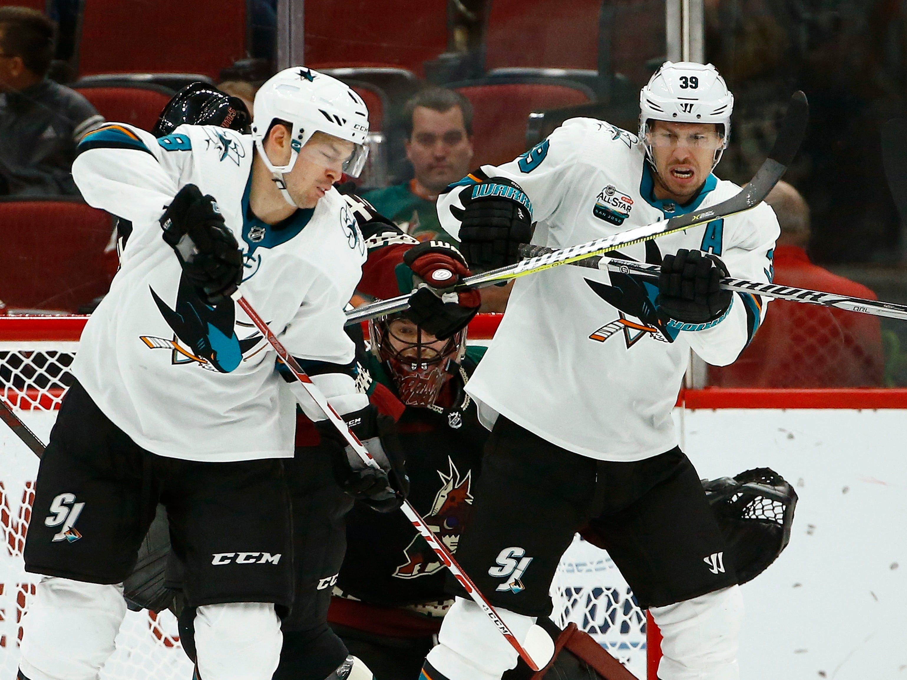 San Jose Sharks center Tomas Hertl, left, and center Logan Couture (39) try to redirect the puck in front of Arizona Coyotes goaltender Adin Hill, middle, during the second period of an NHL hockey game, Saturday, Dec. 8, 2018, in Phoenix.