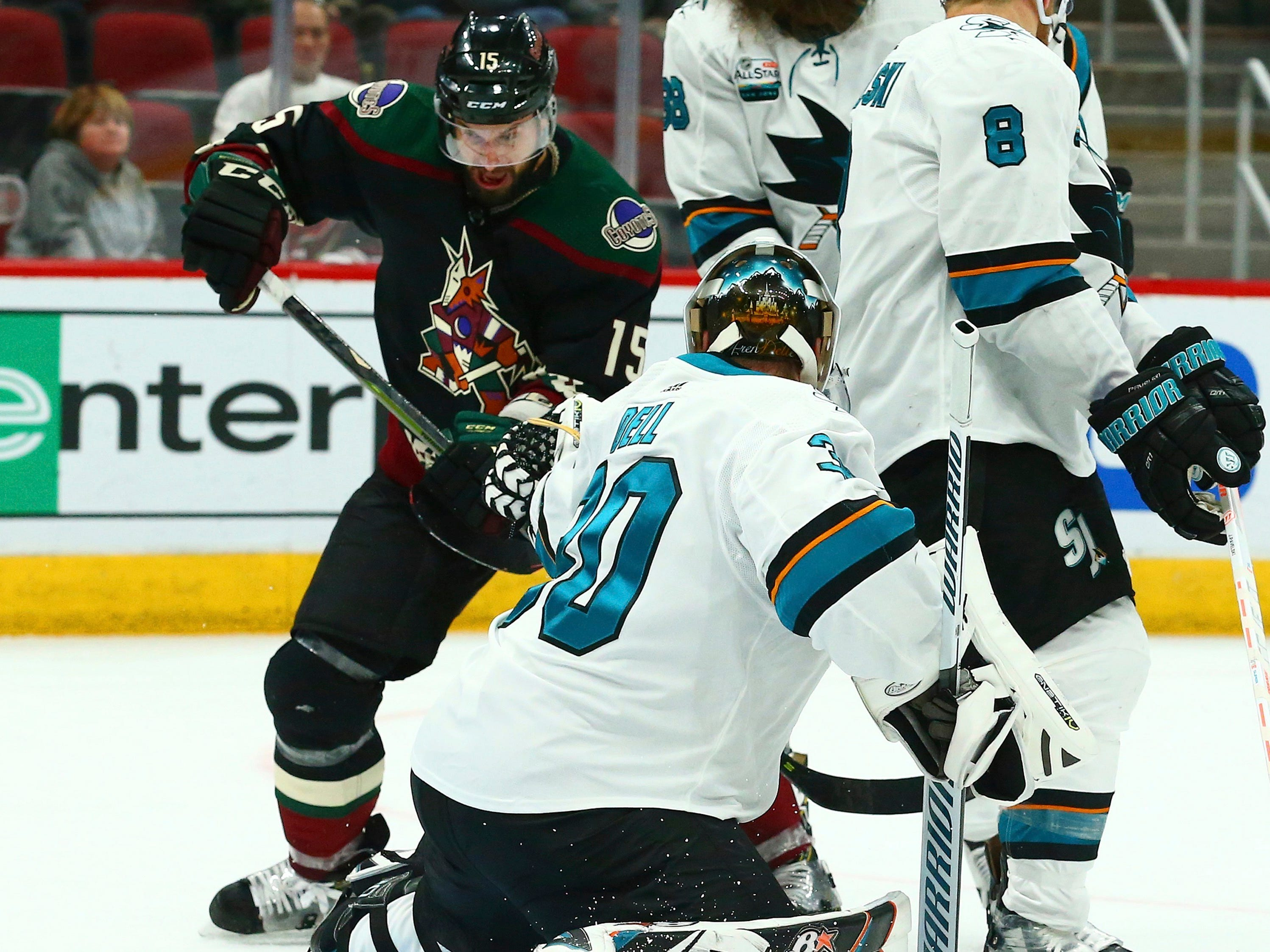 Arizona Coyotes center Brad Richardson (15) redirects the puck past San Jose Sharks goaltender Aaron Dell (30) for a goal during the second period of an NHL hockey game, Saturday, Dec. 8, 2018, in Phoenix.