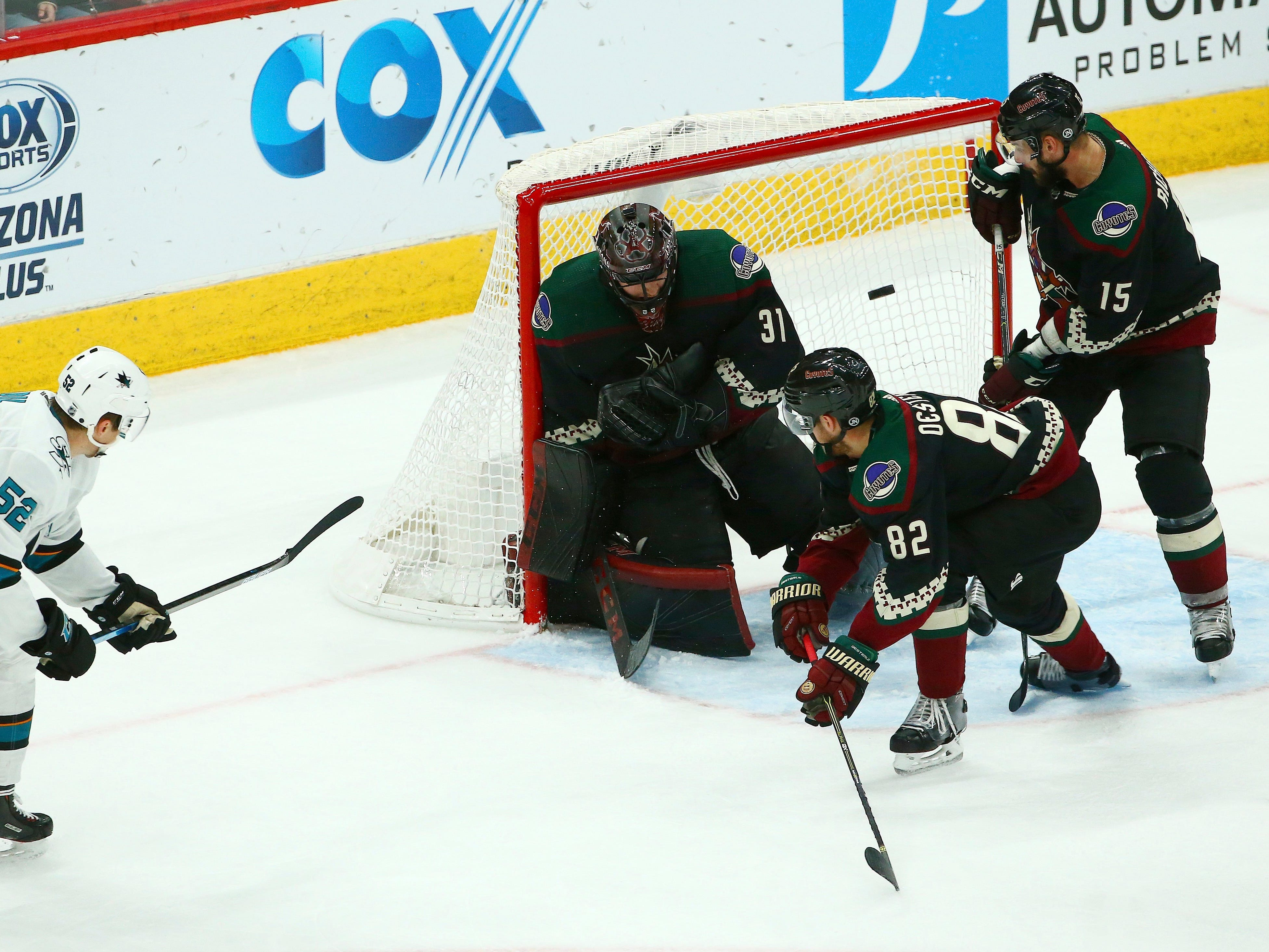 San Jose Sharks center Lukas Radil (52) gets the puck past Arizona Coyotes goaltender Adin Hill (31), defenseman Jordan Oesterle (82) and center Brad Richardson (15) for a goal during the third period of an NHL hockey game, Saturday, Dec. 8, 2018, in Phoenix. The Sharks defeated the Coyotes 5-3.