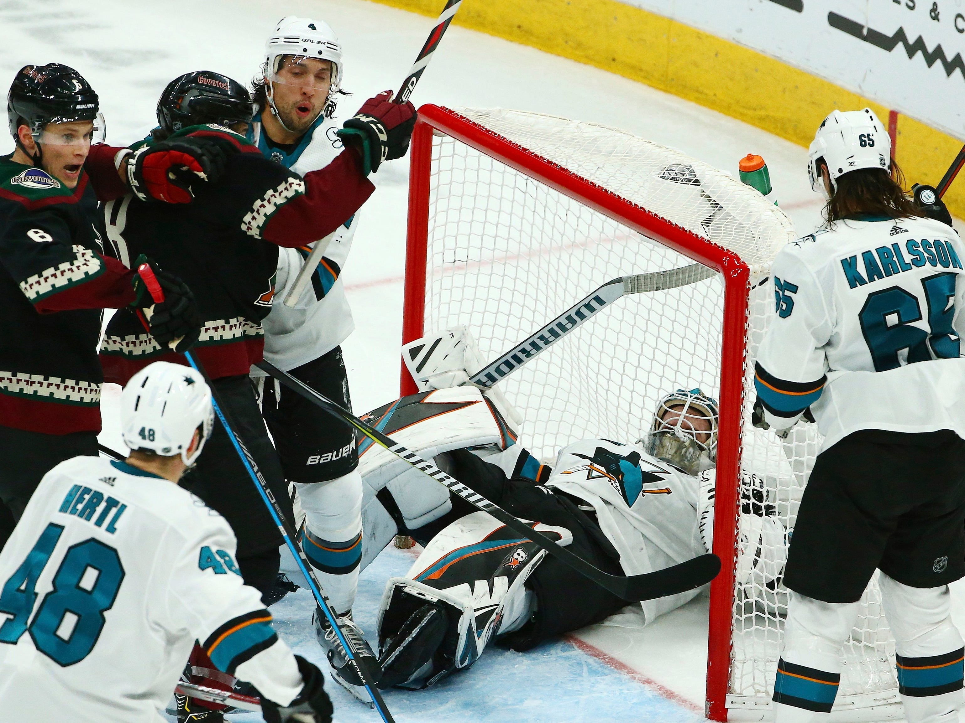 San Jose Sharks goaltender Aaron Dell, middle, makes a save on a shot as Arizona Coyotes defenseman Jakob Chychrun (6) and Coyotes center Nick Schmaltz (8) battle with San Jose Sharks defenseman Brenden Dillon (4) while Sharks center Tomas Hertl (48) and Sharks defenseman Erik Karlsson (65) look on during the third period of an NHL hockey game, Saturday, Dec. 8, 2018, in Phoenix. The Sharks defeated the Coyotes 5-3.