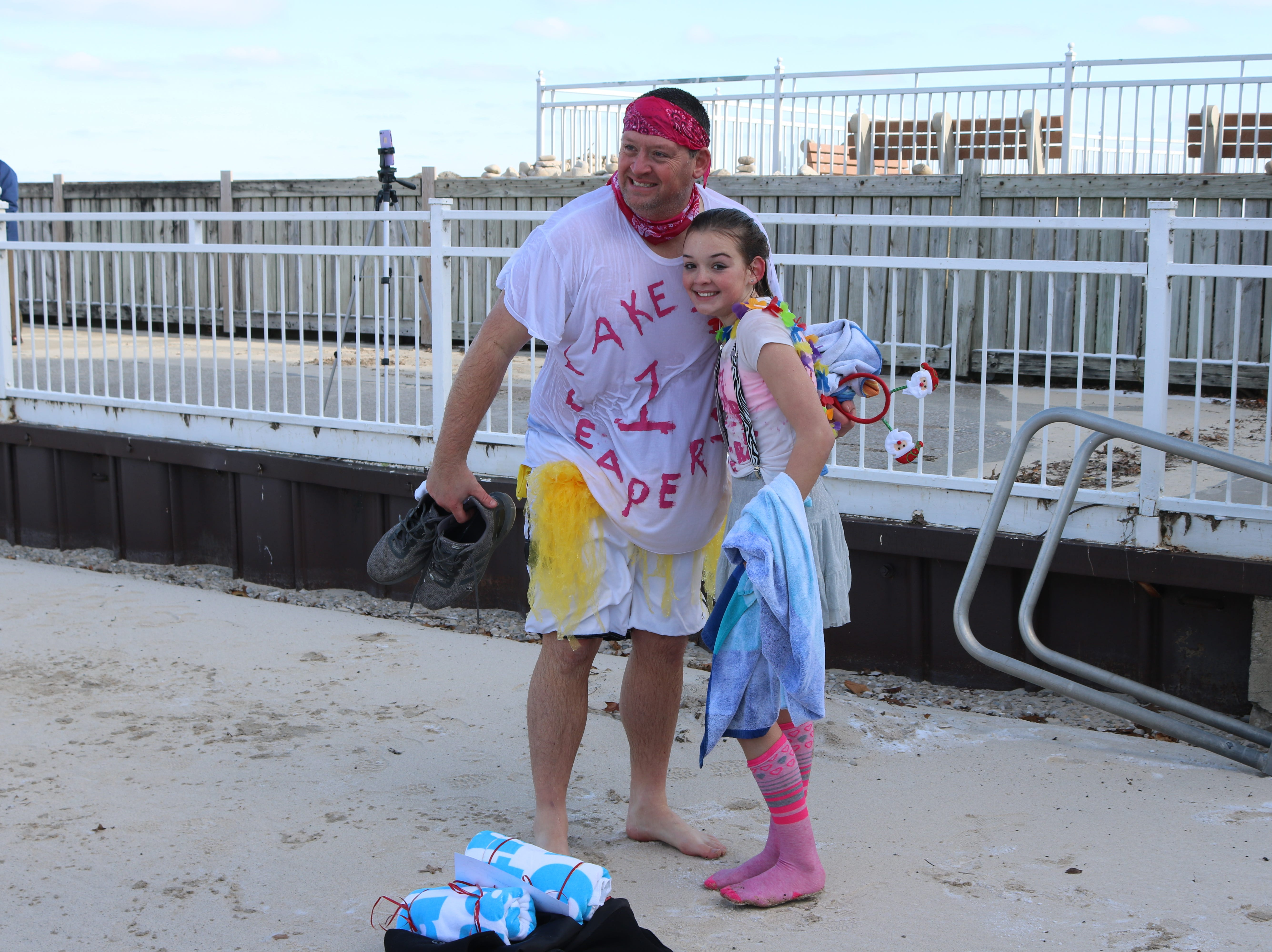 """Chris and Makenna Langford, of Oregon, Ohio, pose for a photo after plunging into Lake Erie for the """"Jingle Jump"""" at Lakeside on Saturday."""
