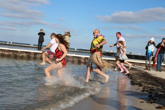 "A few brave souls take a dip in Lake Erie for the first ever ""Jingle Jump"" at Lakeside on Saturday."