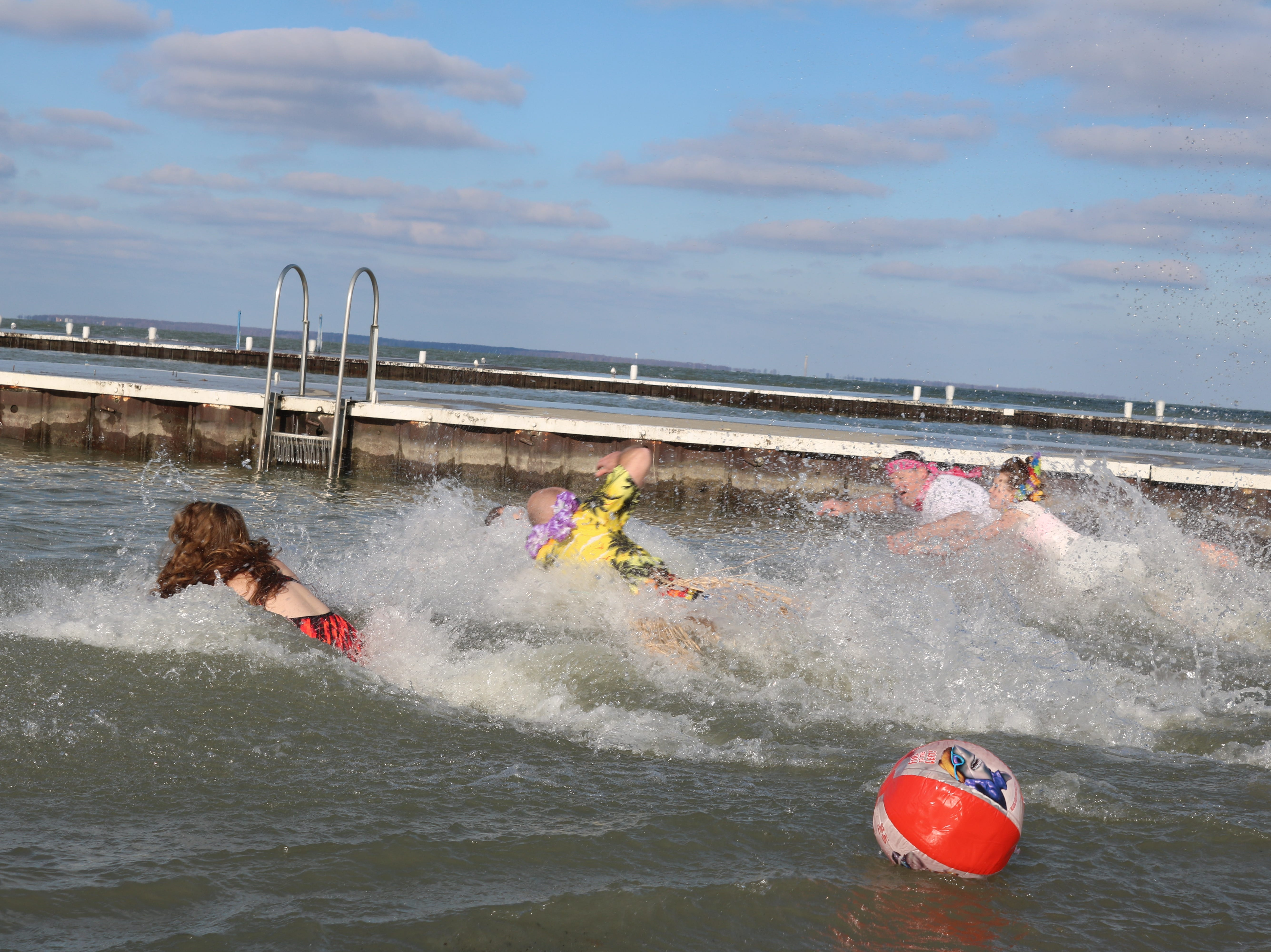 """A few brave souls take a dip in Lake Erie for the first ever """"Jingle Jump"""" at Lakeside on Saturday."""