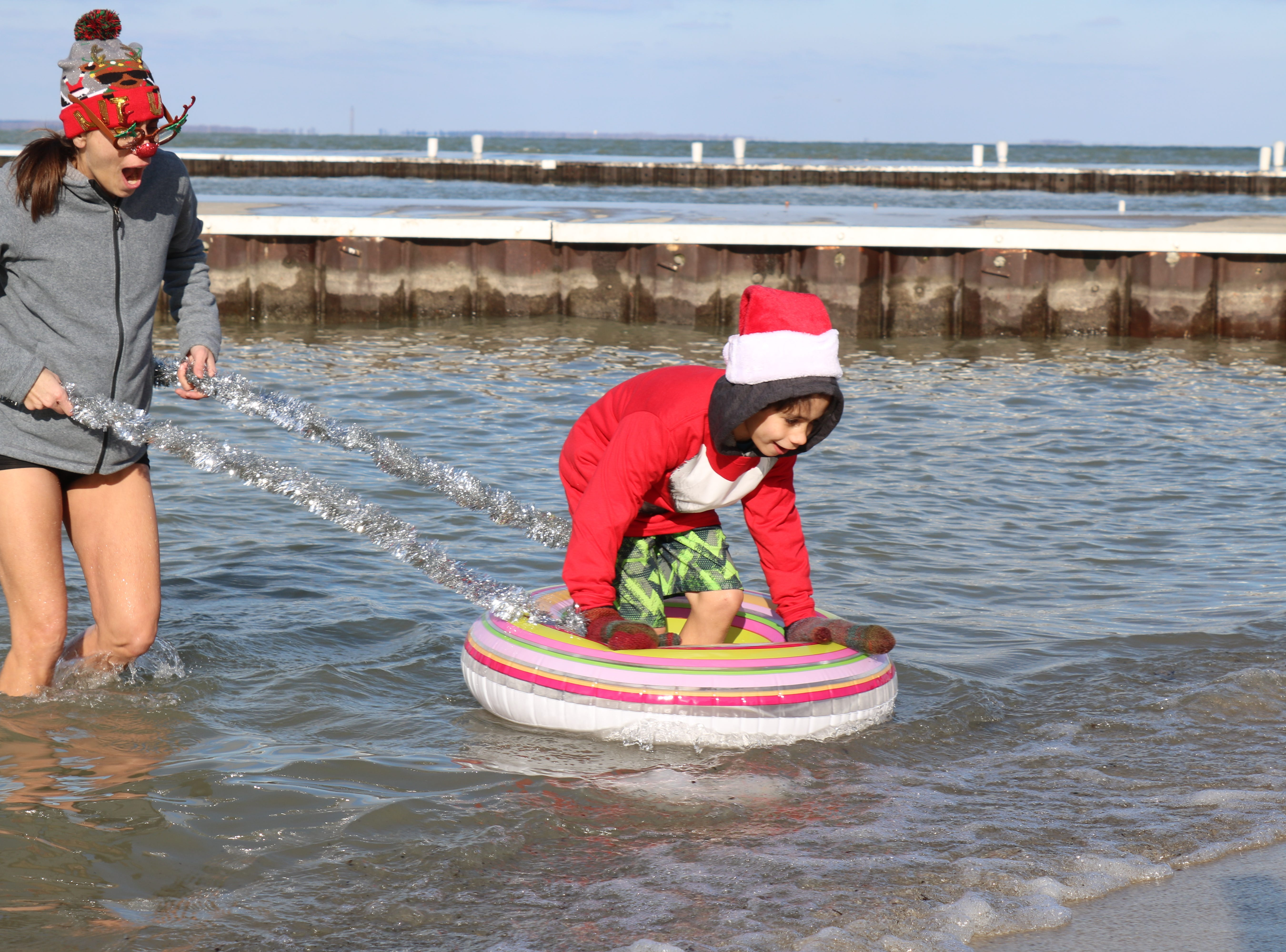 """Laurel and Sebastian Diaz run for the shore after taking a dip in Lake Erie for the """"Jingle Jump"""" at Lakeside on Saturday."""