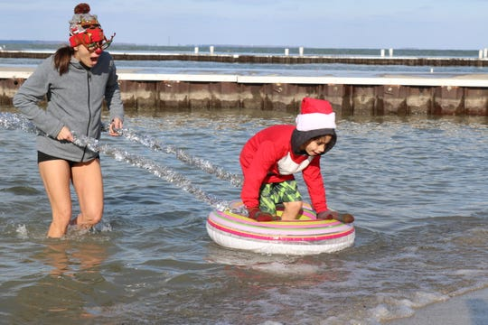 "Laurel and Sebastian Diaz run for the shore after taking a dip in Lake Erie for the ""Jingle Jump"" at Lakeside on Saturday."