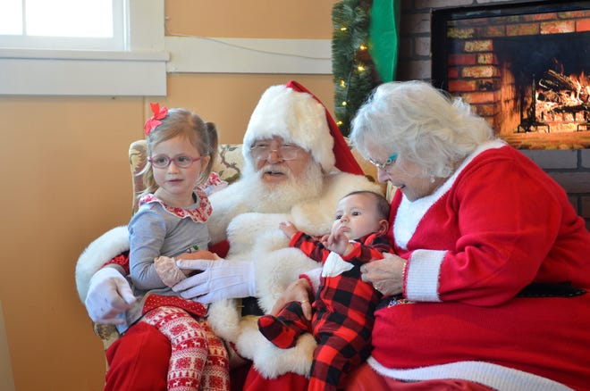 Lucy Anderson, 3, and Myra Anderson, 6 months, visit with Mr. and Mrs. Claus at an event at Fort Gratiot Lighthouse Park on Sunday, Dec. 9, 2018.