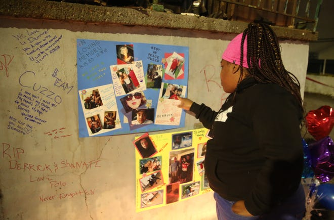 Tamisha Turner, 35, looks at one of the photos at the vigil for the four people who died in a fire in the City of Poughkeepsie on Monday. She used to live in shelters and said the fire highlights the problem of homelessness in the city.