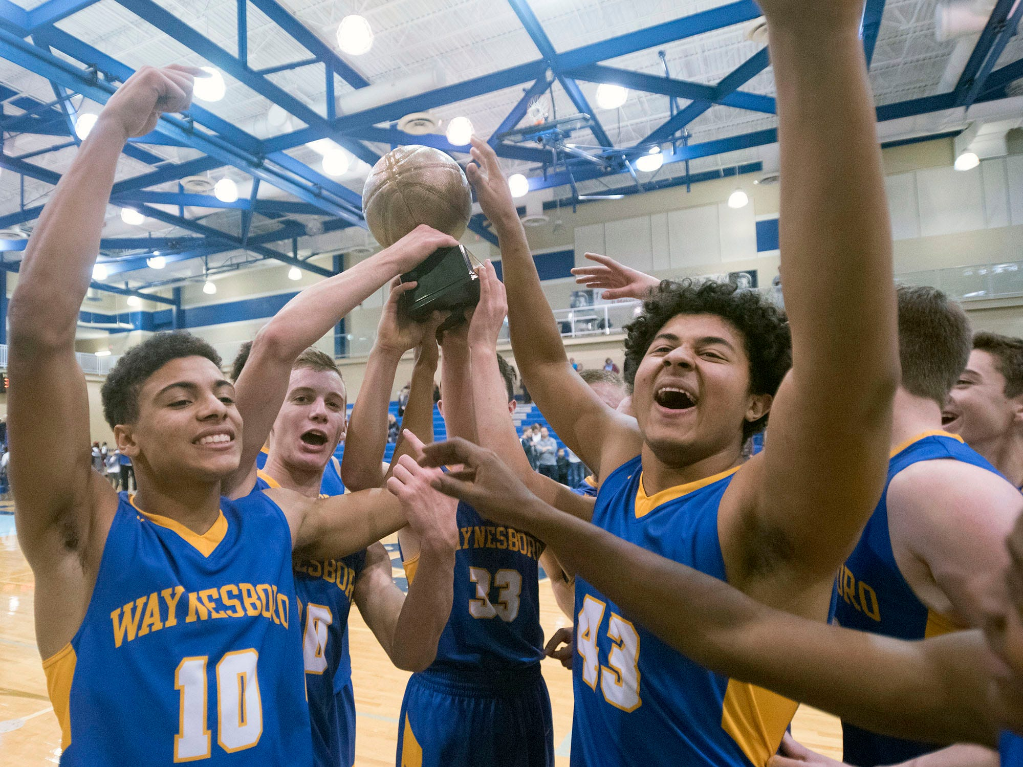Waynesboro teammates carry theeir trophy after defeating Chambersburg 42-39. Chambersburg played Waynesboro during the finals at Franklin County Tip-Off Tournament, Saturday, Dec. 8, 2018.