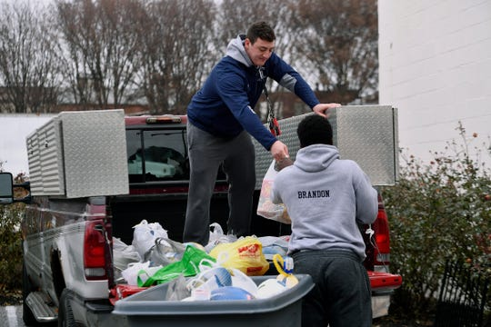 "Raymond Christas, left, and Jamal Brandon, both 17, from Dallastown, unload donated turkeys at the York County Food Bank, Sunday, December 9, 2018. The volunteers from the Dallastown football and wrestling teams, picked up turkeys donated during the first ever ""Bring York Turkey to Church Day."" Six area churches encouraged their members to bring a turkey to worship service during the event.  