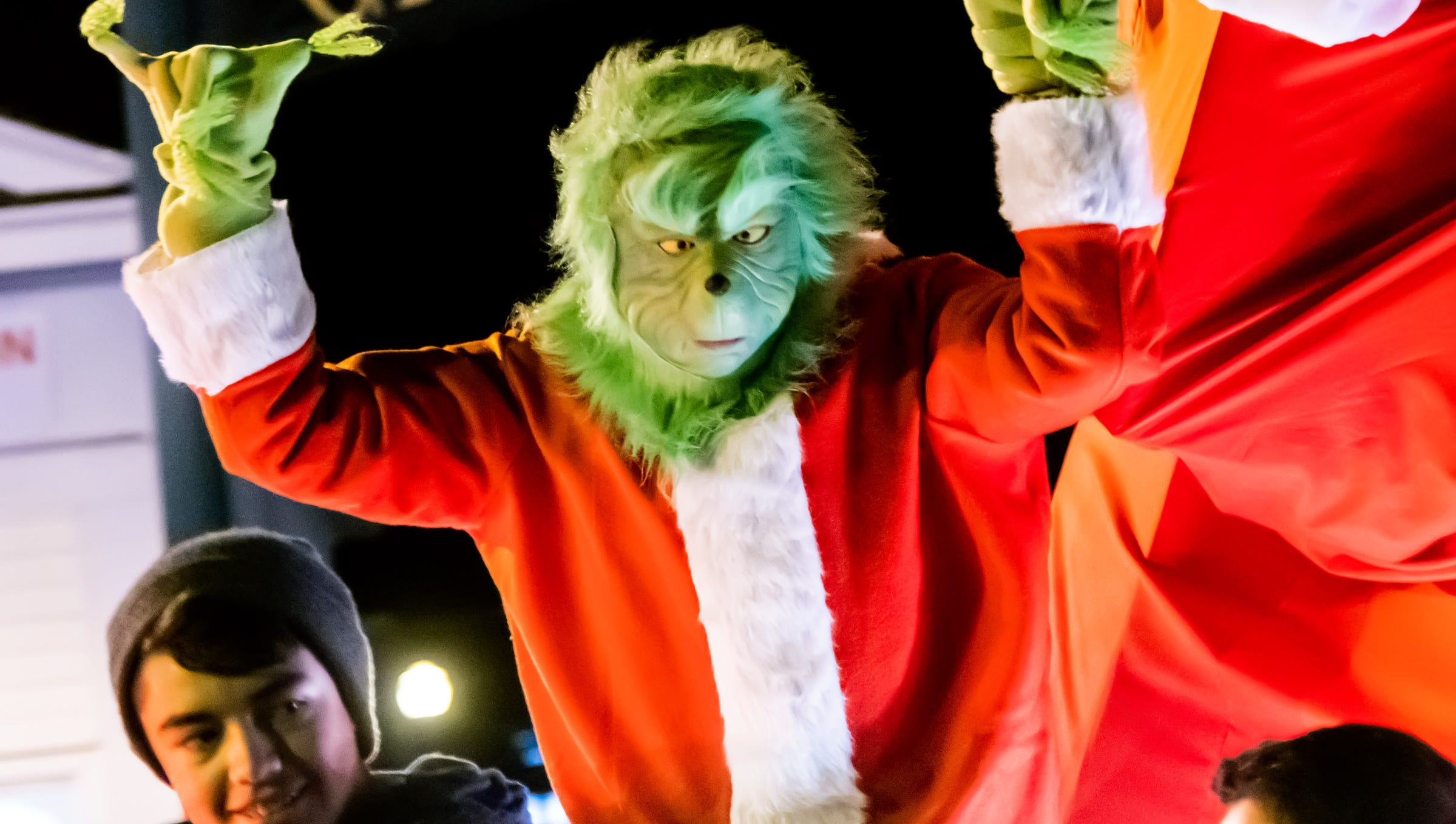 The Grinch peers down from atop his float.