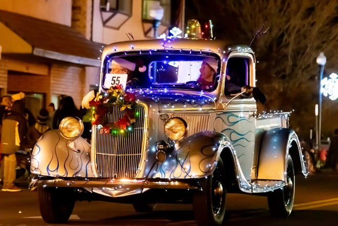 An antique pickup is decked out with holiday lights.