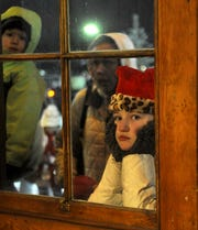 Daisy Schali, 11, of Fernley, peers through a window as she waits in line to visit Santa.