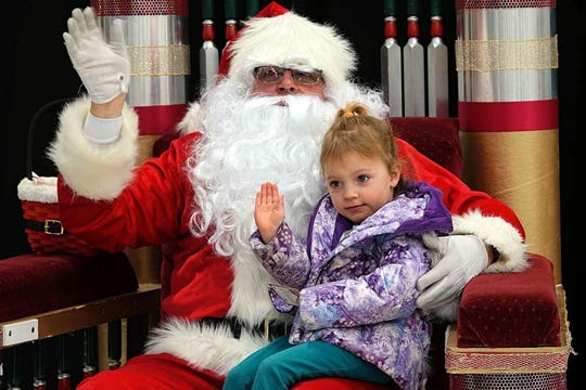 A girl sits on Santa Claus's lap as he greets parents and their children on Dec. 8, 2018 as part of Operation Santa Claus, a charity event that benefits families in need in Reno-Sparks.