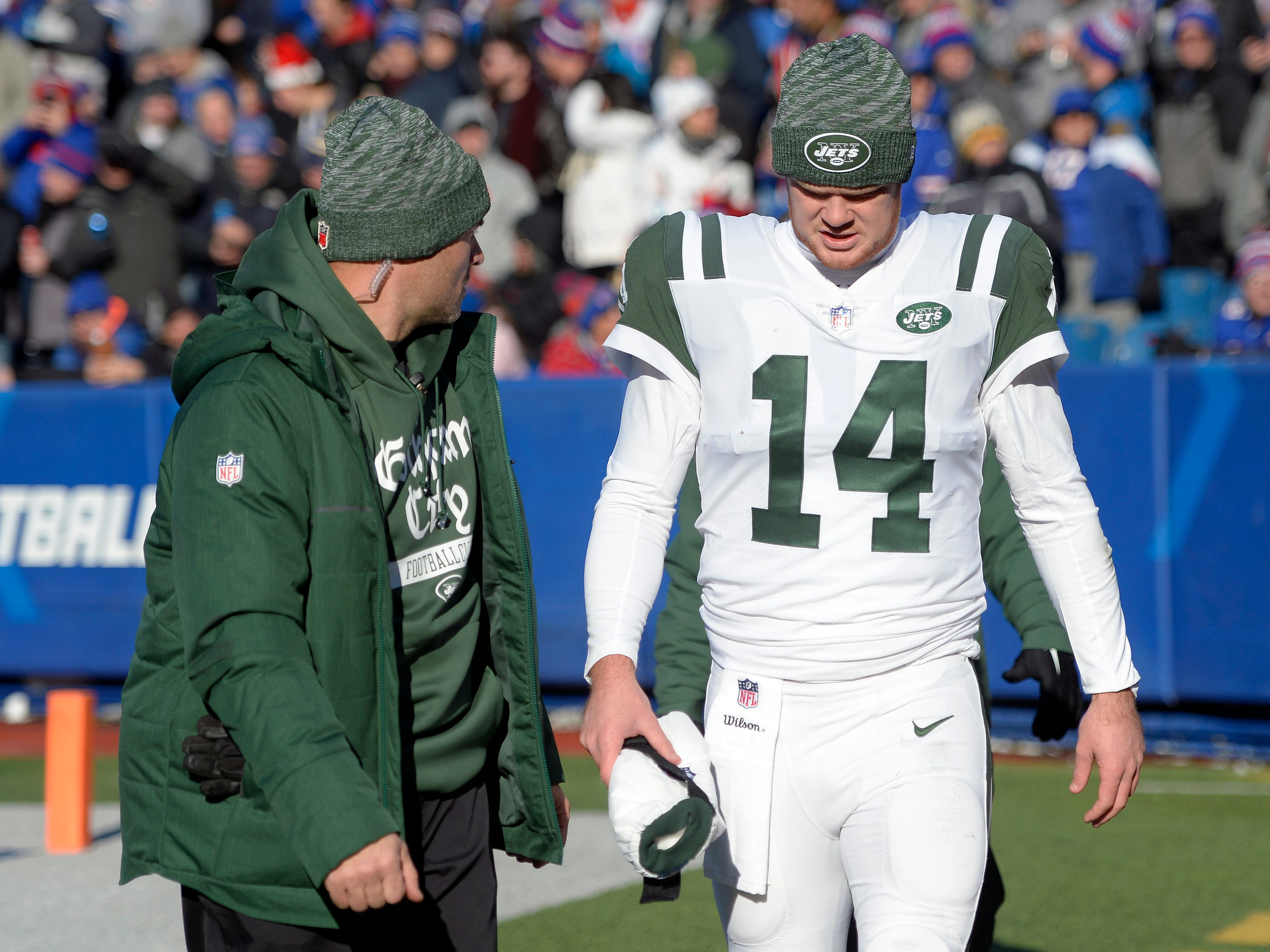 New York Jets quarterback Sam Darnold is escorted toward the tunnel to leave the field during the first half of an NFL football game against the Buffalo Bills, Sunday, Dec. 9, 2018, in Orchard Park, N.Y. (AP Photo/Adrian Kraus)