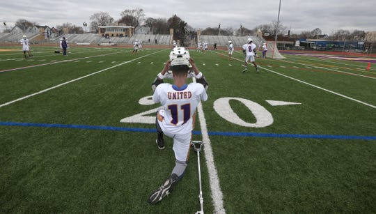 East United midfielder Marquis Reed straps on his helmet before taking the field for warm ups prior to their game against Aquinas at East High School Wednesday, April 18, 2018.   East United is the first varsity lacrosse team based in the City of Rochester.