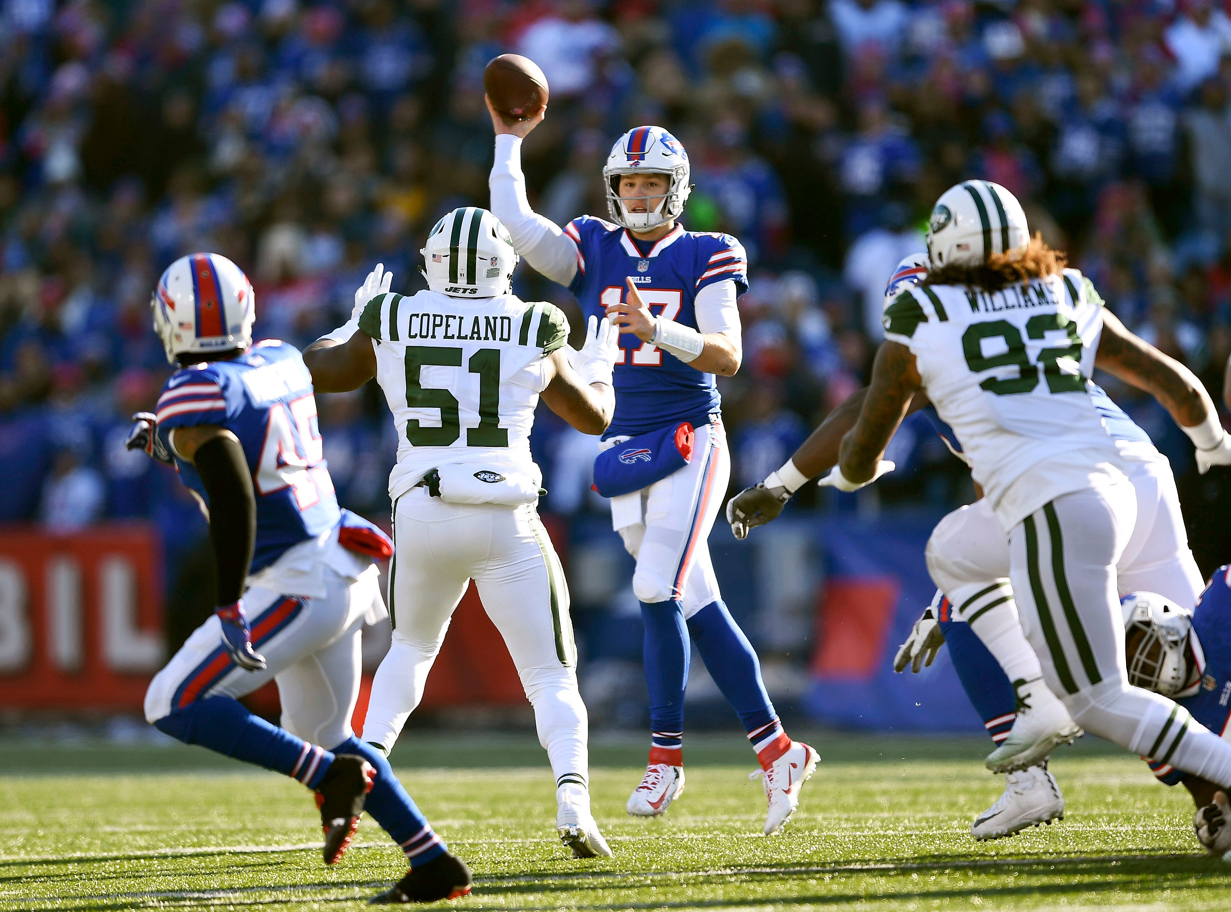 Buffalo Bills quarterback Josh Allen (17) passes under pressure from New York Jets defenders Brandon Copeland (51) and Leonard Williams (92) to running back Marcus Murphy, left, during the first half of an NFL football game, Sunday, Dec. 9, 2018, in Orchard Park, N.Y. (AP Photo/Adrian Kraus)