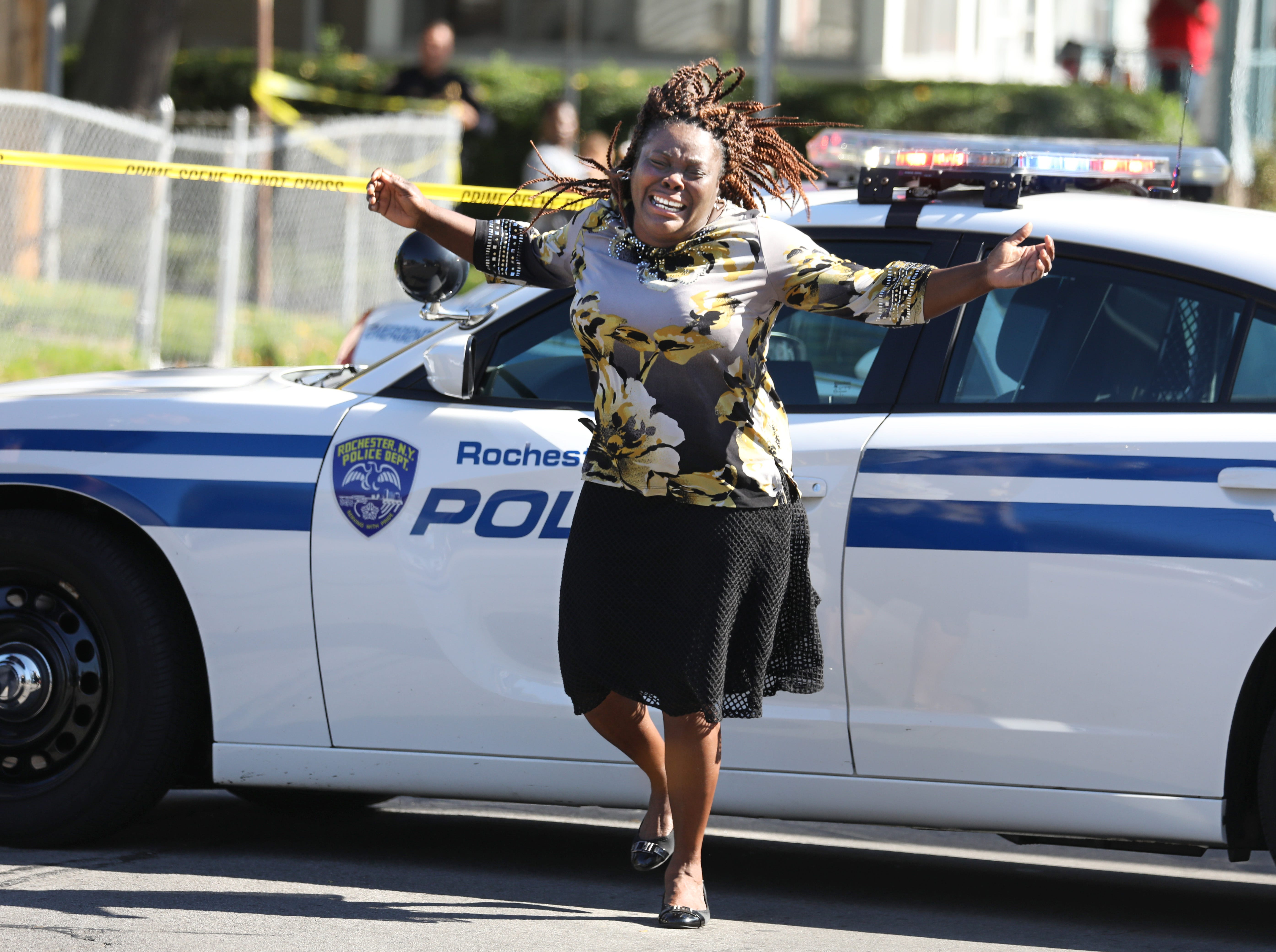 Juliet Blake-Lavan, Rochester, aunt of a shooting suspect, reacts to news that the suspect was killed in a shootout with police. She had stopped at a roadblock near the scene on Bay Street in Rochester on Wednesday, Oct. 10, 2018.