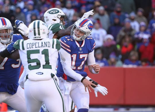 BUFFALO, NY - DECEMBER 09: Josh Allen #17 of the Buffalo Bills is hit as he throws in the second quarter during NFL game action as Buster Skrine #41 of the New York Jets is assessed a roughing-the-passer penalty at New Era Field on December 9, 2018 in Buffalo, New York. (Photo by Tom Szczerbowski/Getty Images)