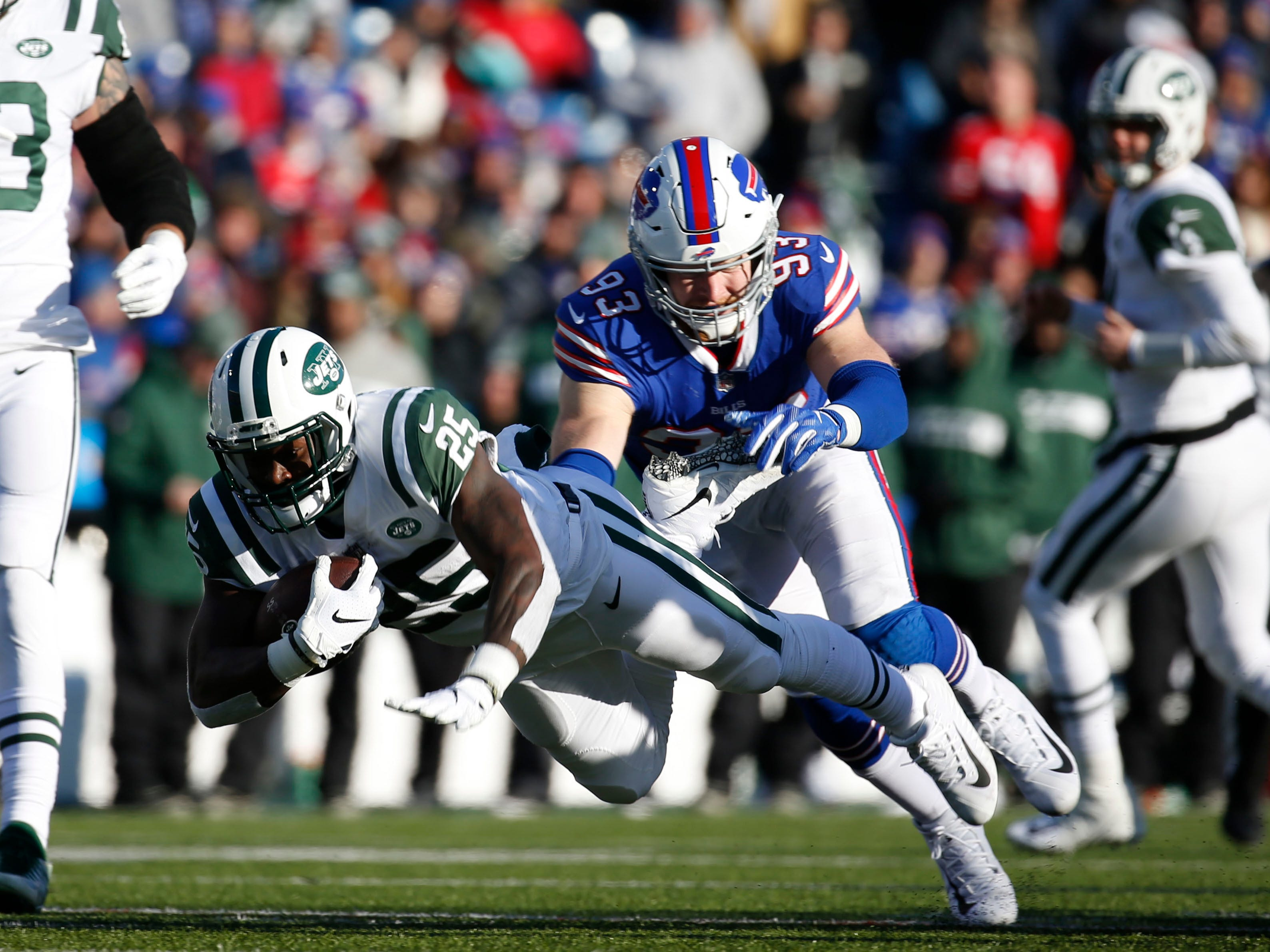 Dec 9, 2018; Orchard Park, NY, USA; New York Jets running back Elijah McGuire (25) runs the ball and gets tackled by Buffalo Bills defensive end Trent Murphy (93) during the first half at New Era Field. Mandatory Credit: Timothy T. Ludwig-USA TODAY Sports