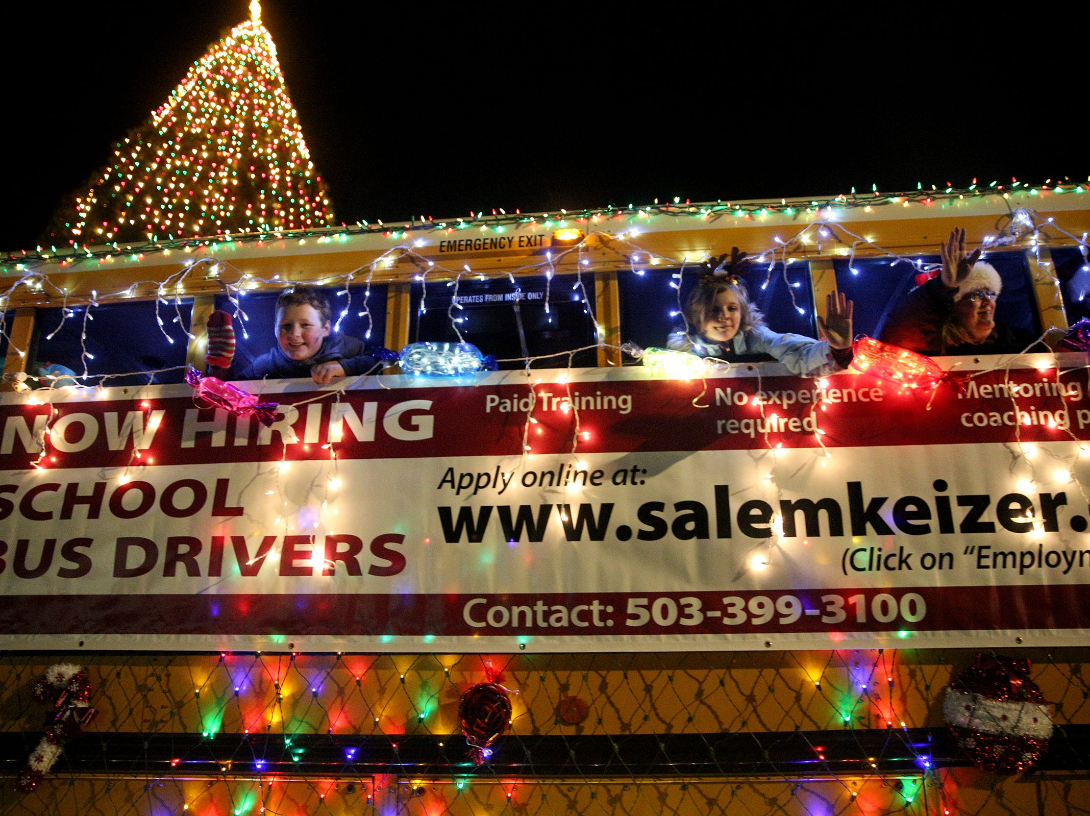Salem-Keizer Public Schools showcases their lit-up school bus during the Keizer Holiday Lights Parade in Keizer on Saturday, Dec. 8, 2018.