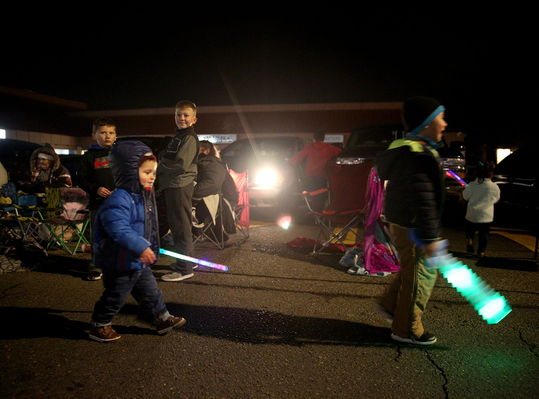 Two-year-old Nico Hernandez chases another child with his light-up sword during the Keizer Holiday Lights Parade in Keizer on Saturday, Dec. 8, 2018.