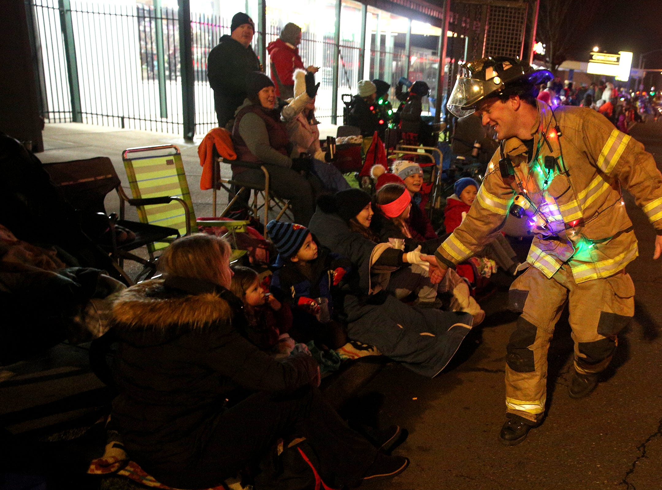 A Salem Fire Department firefighter high fives parade attendees during the Keizer Holiday Lights Parade in Keizer on Saturday, Dec. 8, 2018.
