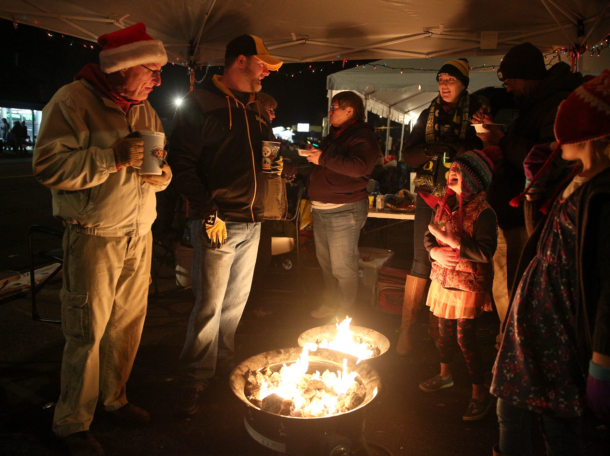 Keizer residents, the Harbaugh family and their friends, warm up by their fire pit before the Keizer Holiday Lights Parade on Saturday, Dec. 8, 2018.