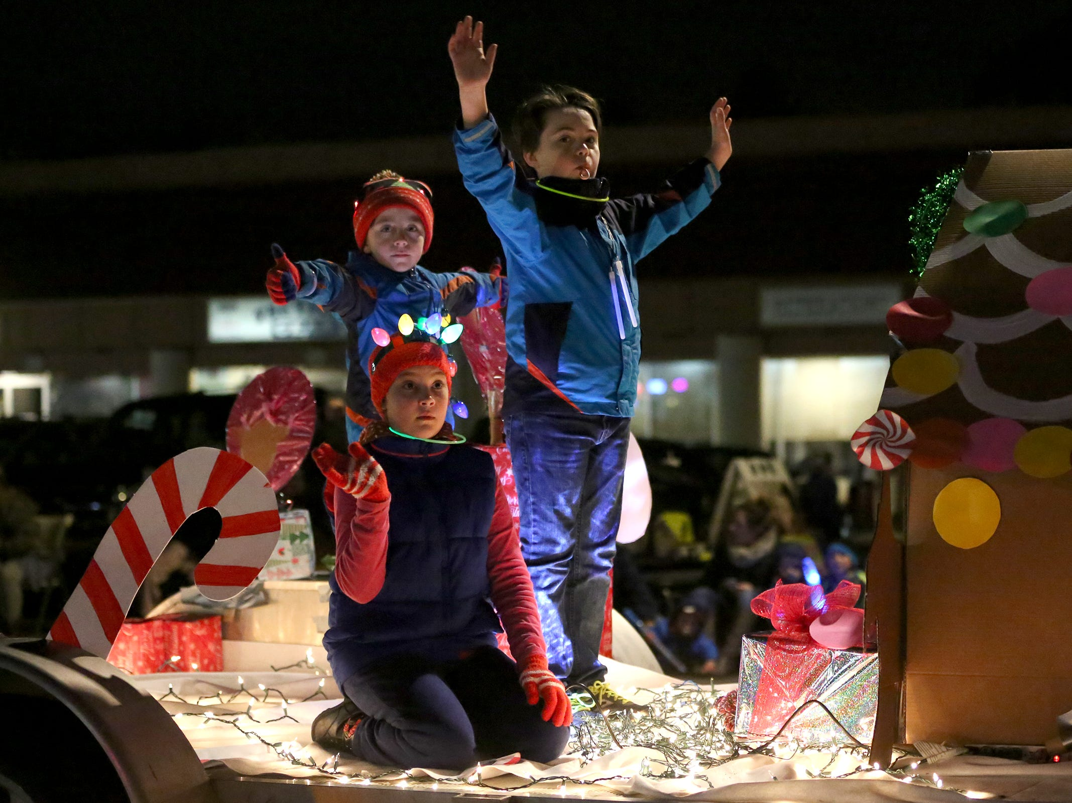 Children on a Candy Land themed float wave during the Keizer Holiday Lights Parade in Keizer on Saturday, Dec. 8, 2018.