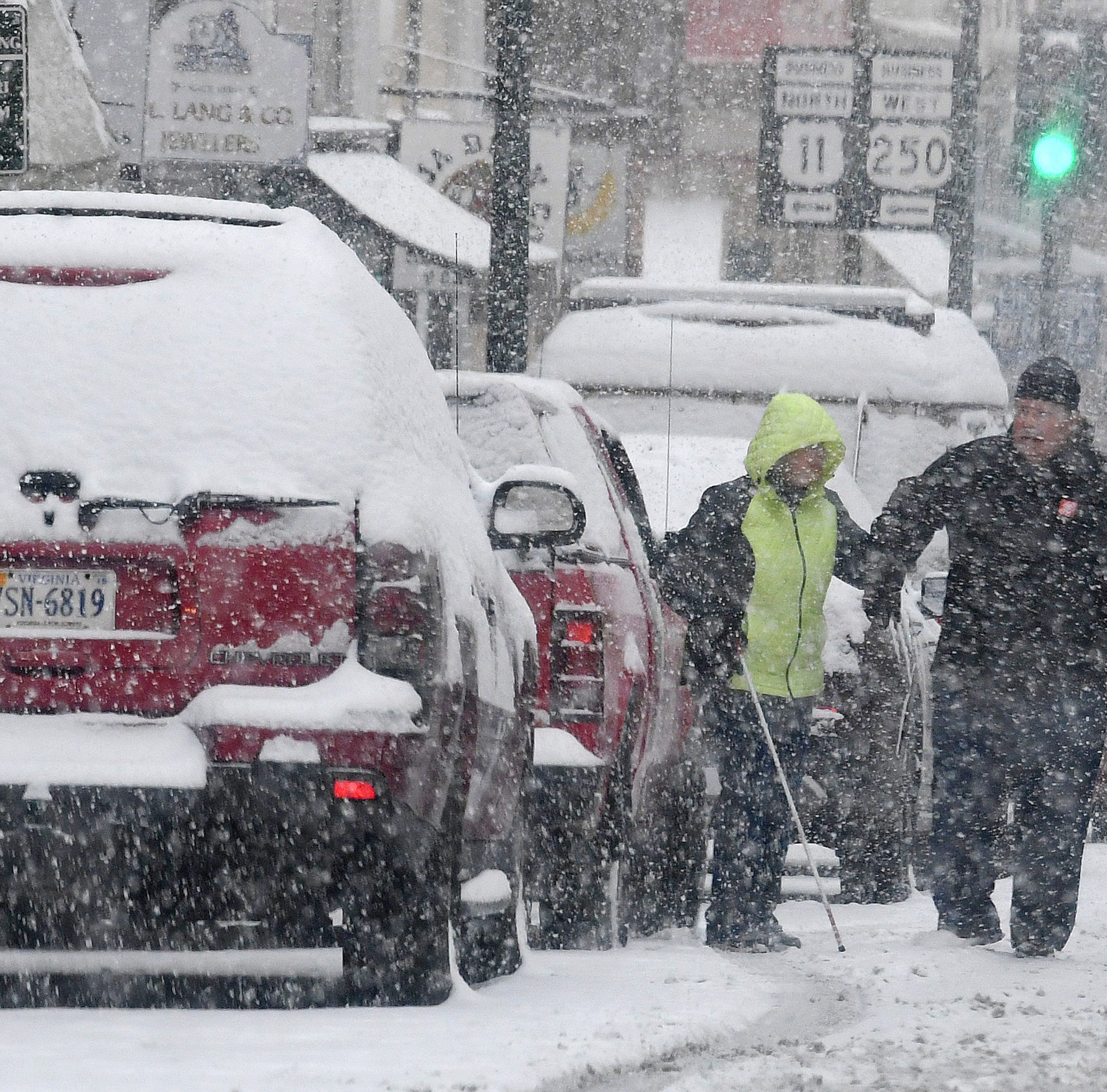 Snow continues to fall as a man assists a lady after parking on West Beverley Street in downtown Staunton on Sunday, Dec. 9, 2018.