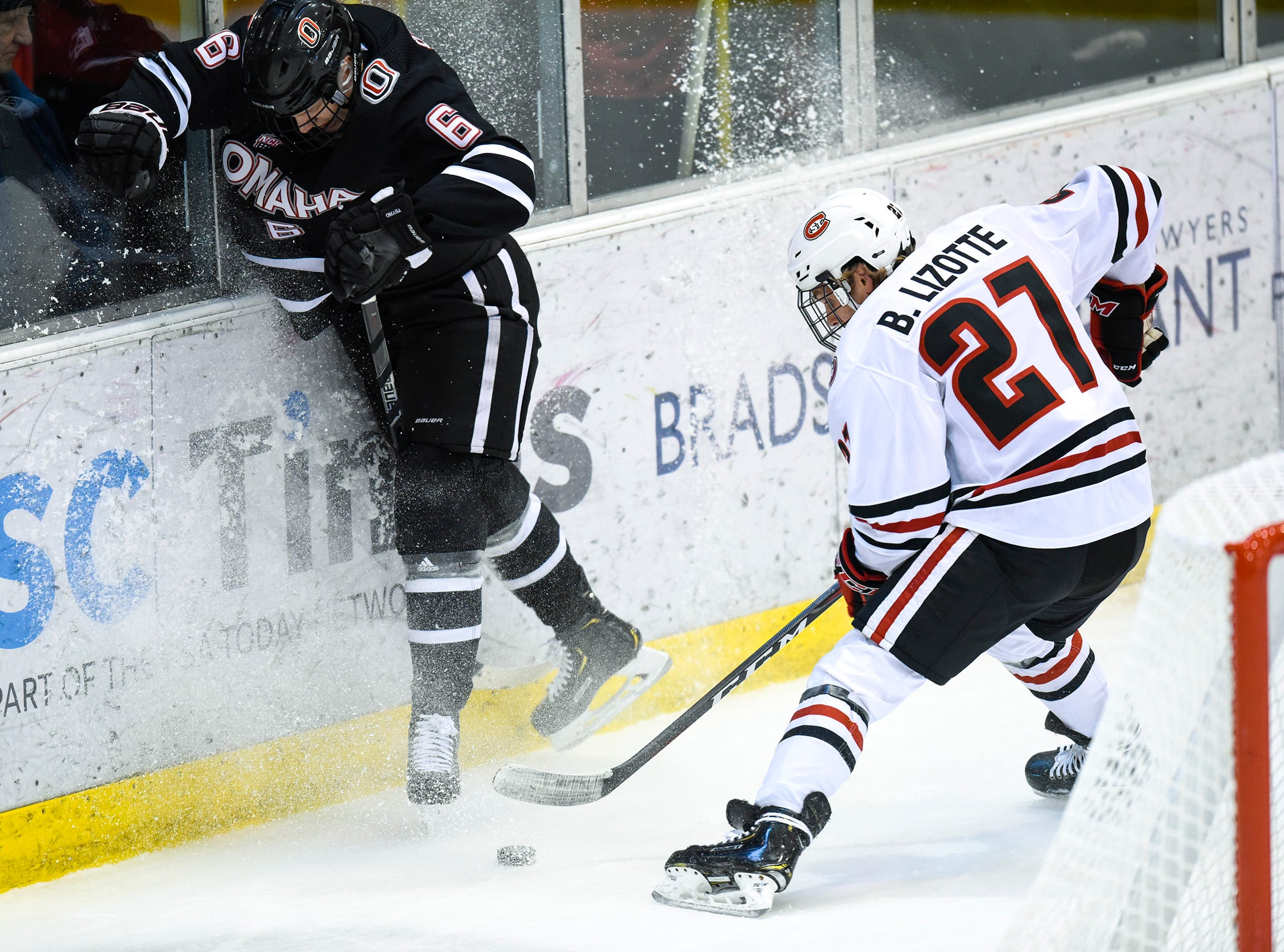 Nebraska-Omaha's Lukas Buchta and St. Cloud State's Blake Lizotte battle for the puck behind the goal during the first period Saturday, Dec. 8, at the Herb Brooks National Hockey Center.