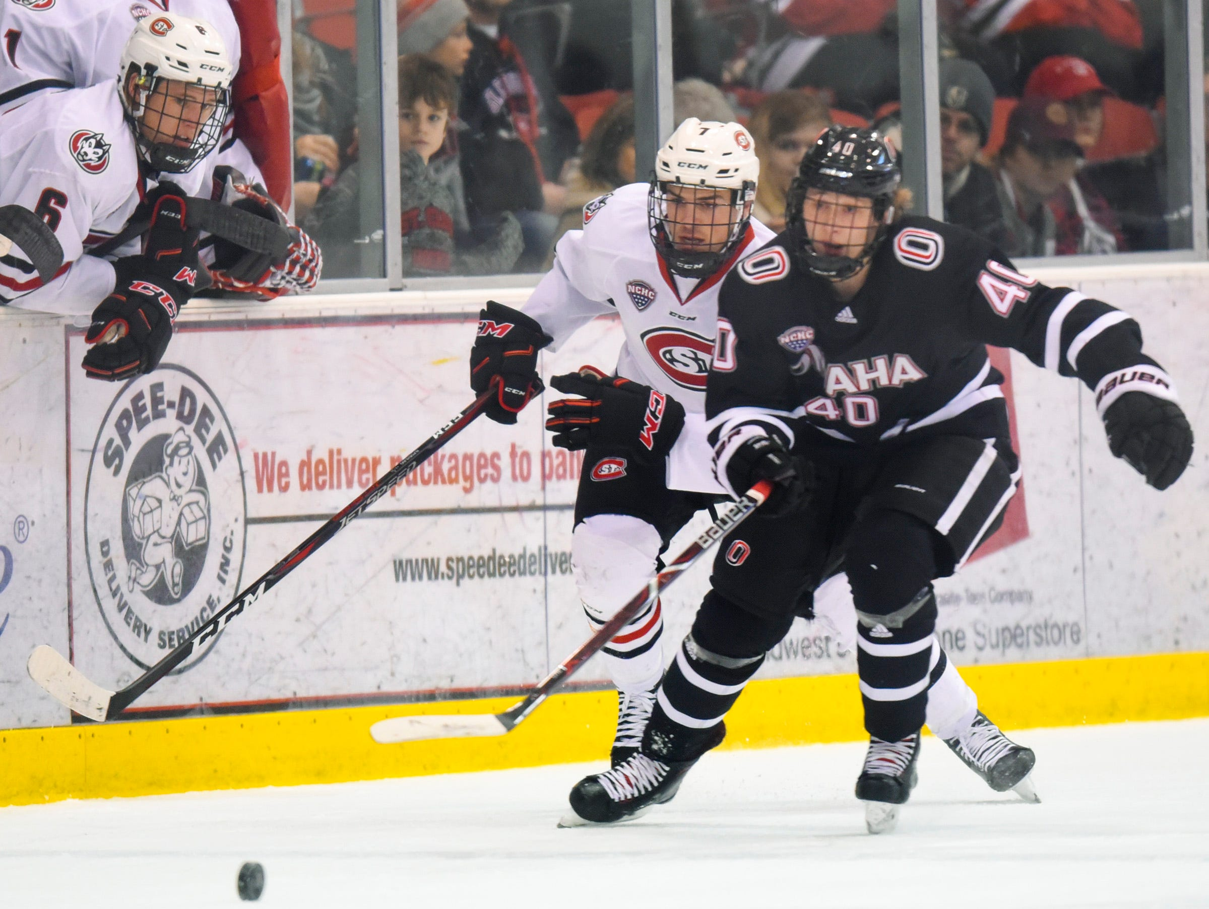 St. Cloud State's Nick Poehling and Nebraska-Omaha's Tyler Weiss chase a loose puck during the first period Saturday, Dec. 8, at the Herb Brooks National Hockey Center.