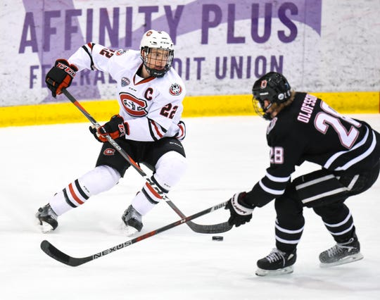 St. Cloud State's Jimmy Schuldt takes the puck around Nebraska-Omaha's Fredrik Olofsson during the first period Saturday, Dec. 8, at the Herb Brooks National Hockey Center.