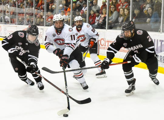 St. Cloud State's Ryan Poehling, 11, is shut down by Nebraska-Omaha's Riley Alferd, left, and Jason Smallidge as he tries to score during the first period Saturday, Dec. 8, at the Herb Brooks National Hockey Center.