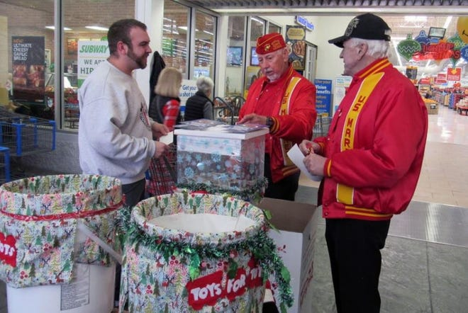 Marines Gene Rose and Gene Wright meet with donors in front of a Toys for Tots collection display at the Walmart store in St. George in this undated submitted photograph.