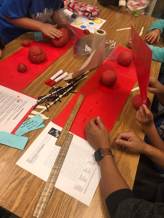 Students and parents at J.L. Bowler Elementary learn about the true sizes of the planets with the Planet Play-Doh activity at the school's first-ever family science night.