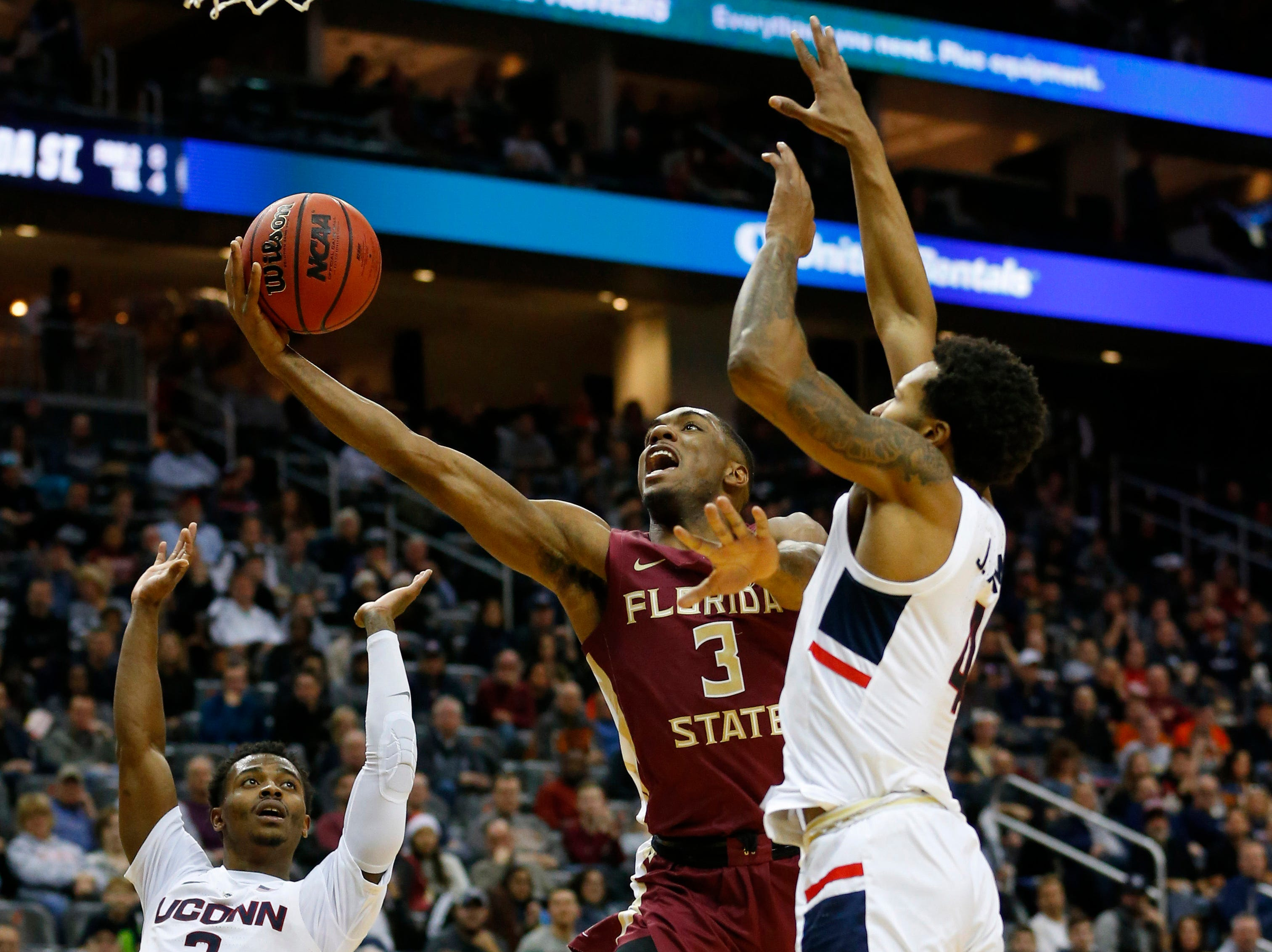Dec 8, 2018; Newark, NJ, USA; Florida State Seminoles guard Trent Forrest (3) goes to the basket against Connecticut Huskies guard Alterique Gilbert (3) and guard Jalen Adams (4) during the first half at Prudential Center. Mandatory Credit: Noah K. Murray-USA TODAY Sports