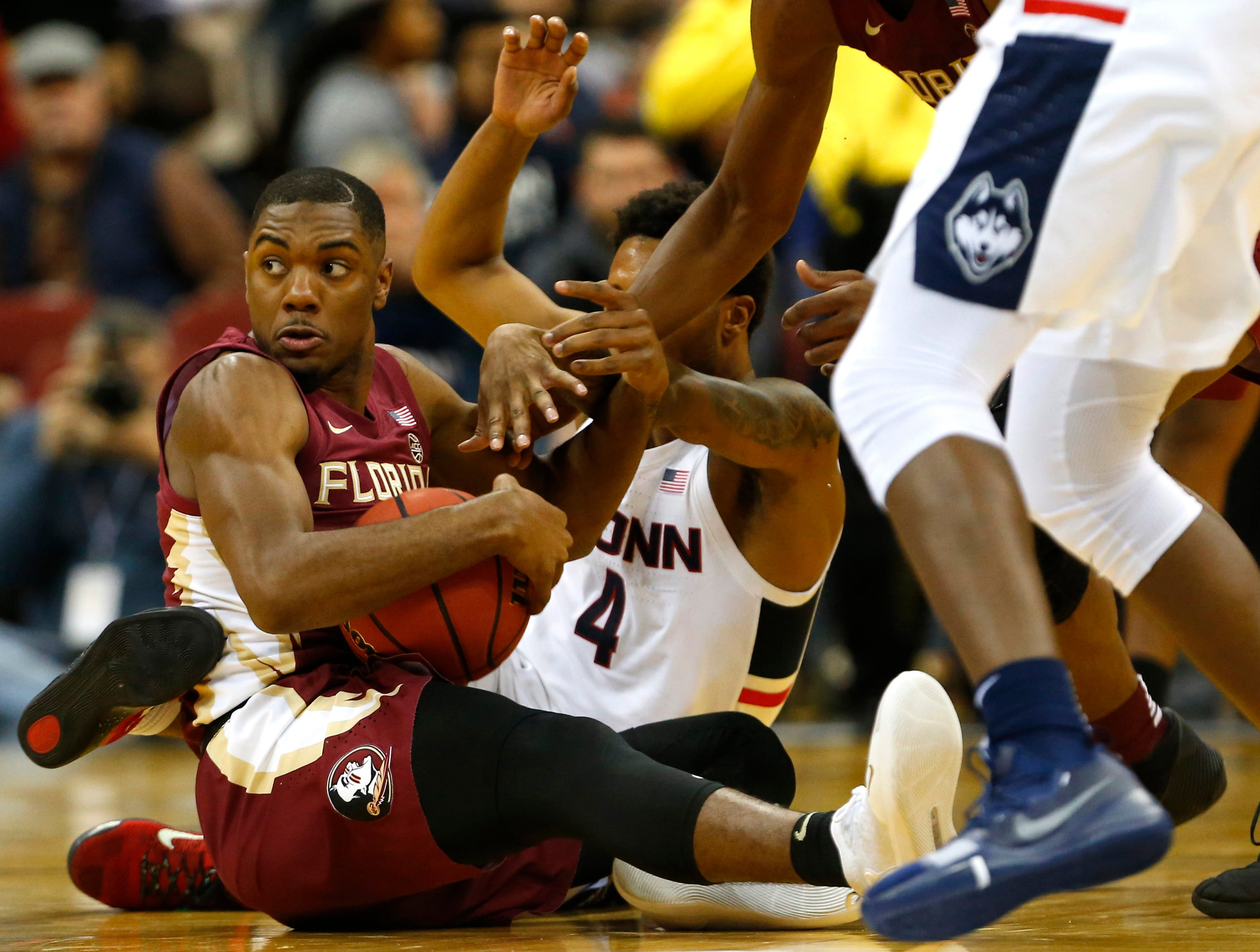 Dec 8, 2018; Newark, NJ, USA; Florida State Seminoles guard Trent Forrest (3) takes a loose ball f4om Connecticut Huskies guard Jalen Adams (4) during the first half at Prudential Center. Mandatory Credit: Noah K. Murray-USA TODAY Sports