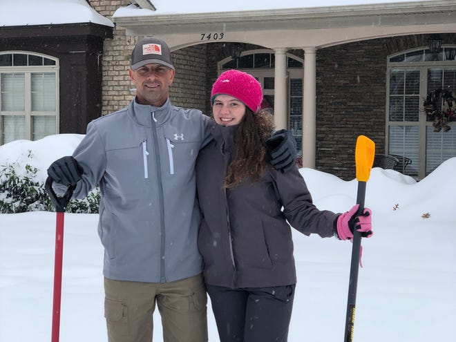 Link Jarrett with daughter Dawson, 16, shoveling snow in Summerfield, North Carolina, Sunday.