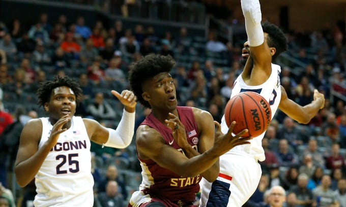Dec 8, 2018; Newark, NJ, USA; Florida State Seminoles guard Terance Mann (14) passes the ball around Connecticut Huskies forward Tyler Polley (12) during the first half at Prudential Center. Mandatory Credit: Noah K. Murray-USA TODAY Sports