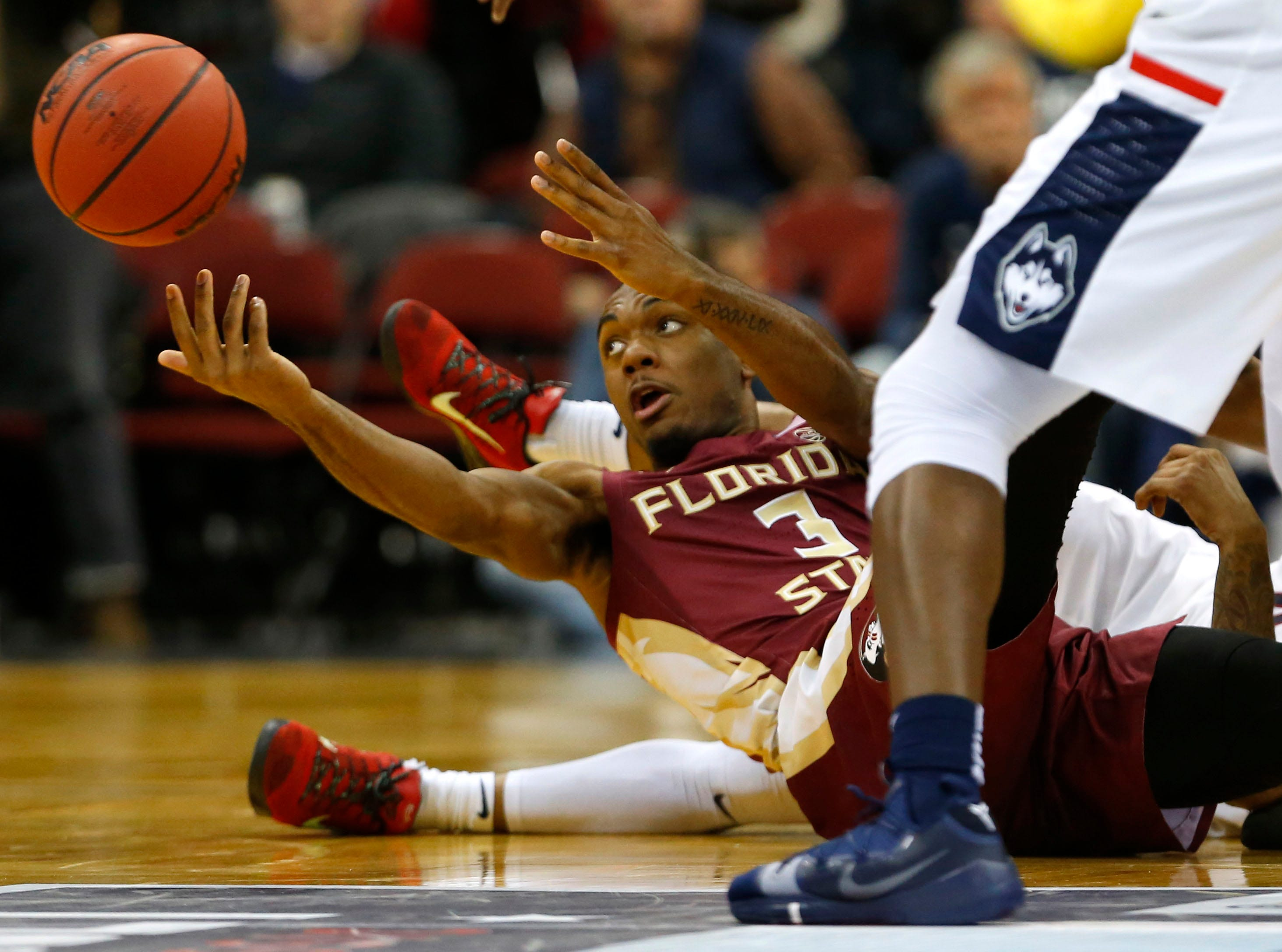 Dec 8, 2018; Newark, NJ, USA; Florida State Seminoles guard Trent Forrest (3) passes a loose ball away from Connecticut Huskies defenders during the first half at Prudential Center. Mandatory Credit: Noah K. Murray-USA TODAY Sports