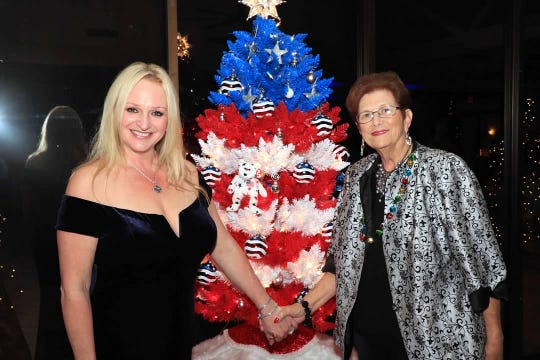 Lori Finkel, left, and Jane Rowley pose in front of the All-American Tree at CASTLE's Holiday Magic Gala on Dec. 1, 2018, at the St. Lucie Golf Trail Clubhouse.