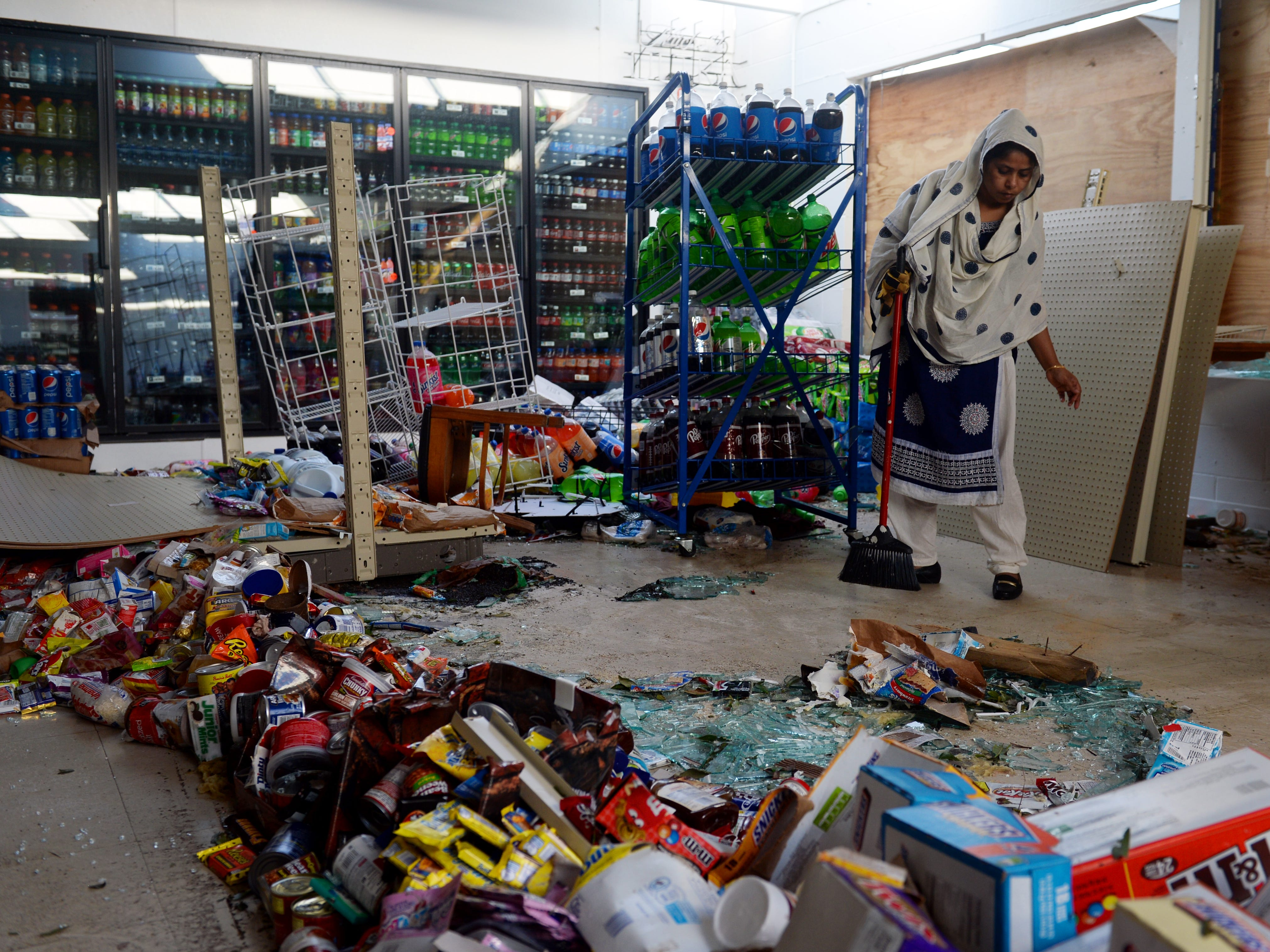 Oct. 12, 2018, Panama City, FL, USA; Khodaza Khatun Popi works to clean spoiled food, broken glass and water from the floor of the Shop N Go Jr. convenience store two days after Hurricane Michael blew through Panama City. Mandatory Credit: Patrick Dove/Treasure Coast News via USA Today NETWORK