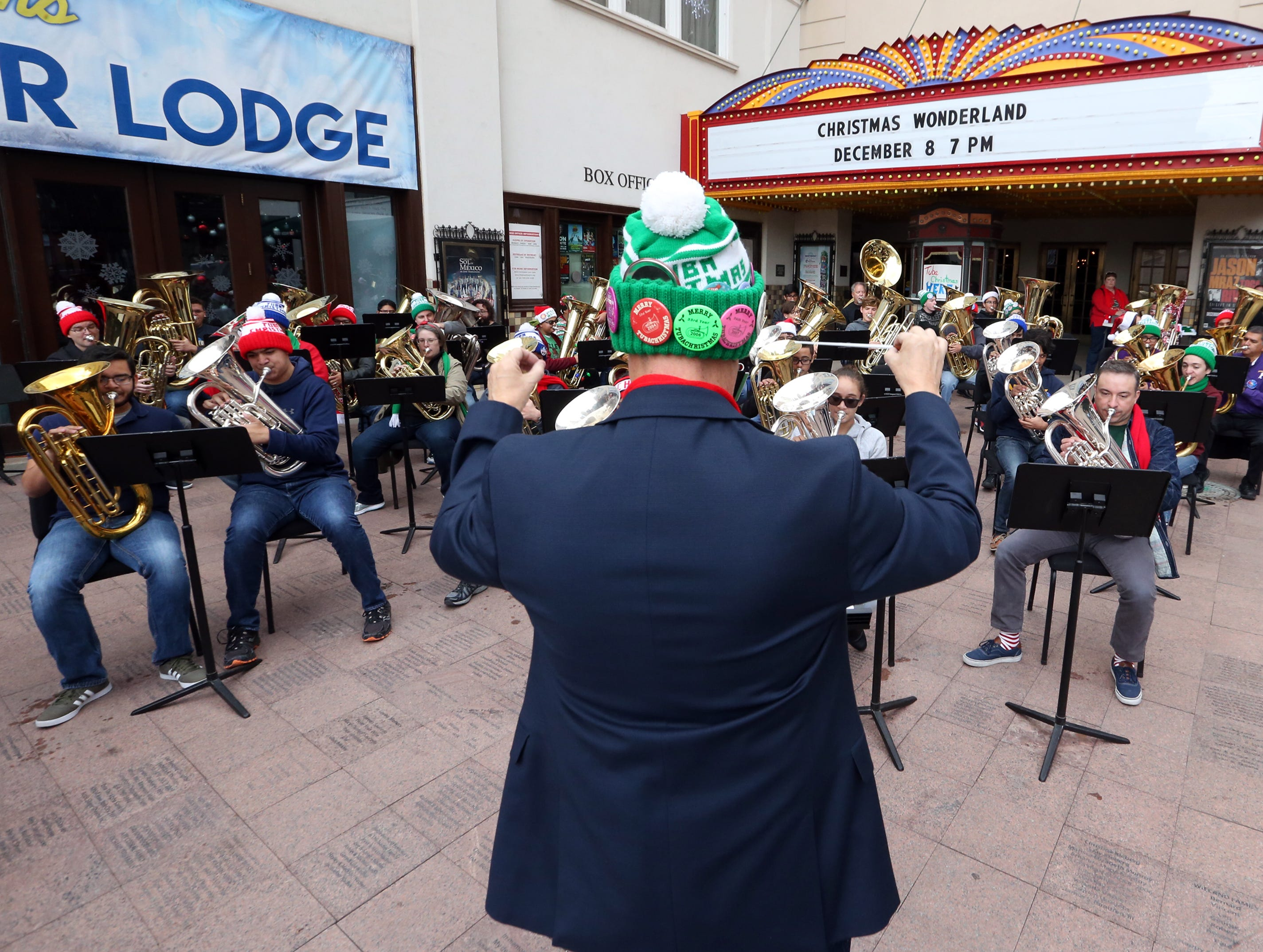 Bryan Andrade leads a group of tuba and baritone players in a number of Christmas favorites during the annual Tuba Christmas concert outside the Plaza Theatre Saturday in downtown El Paso.