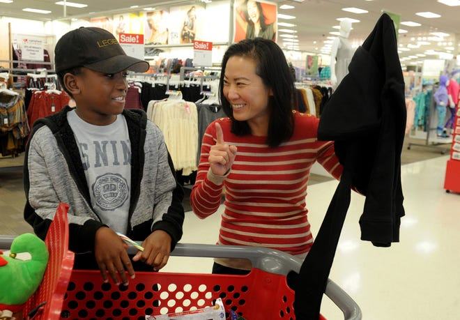 Samuel Opoku gets help from Kristina Tansavatdi, a member of the Rotary Club of Westlake Village, as he picks clothes and a gift for his mom. The club hosted a shopping spree at Target for 36 members of the Boys & Girls Club. The children, each with $110 to spend, were paired with 36 volunteers, and they also got two $10 gift cards so they could buy gifts for someone else.