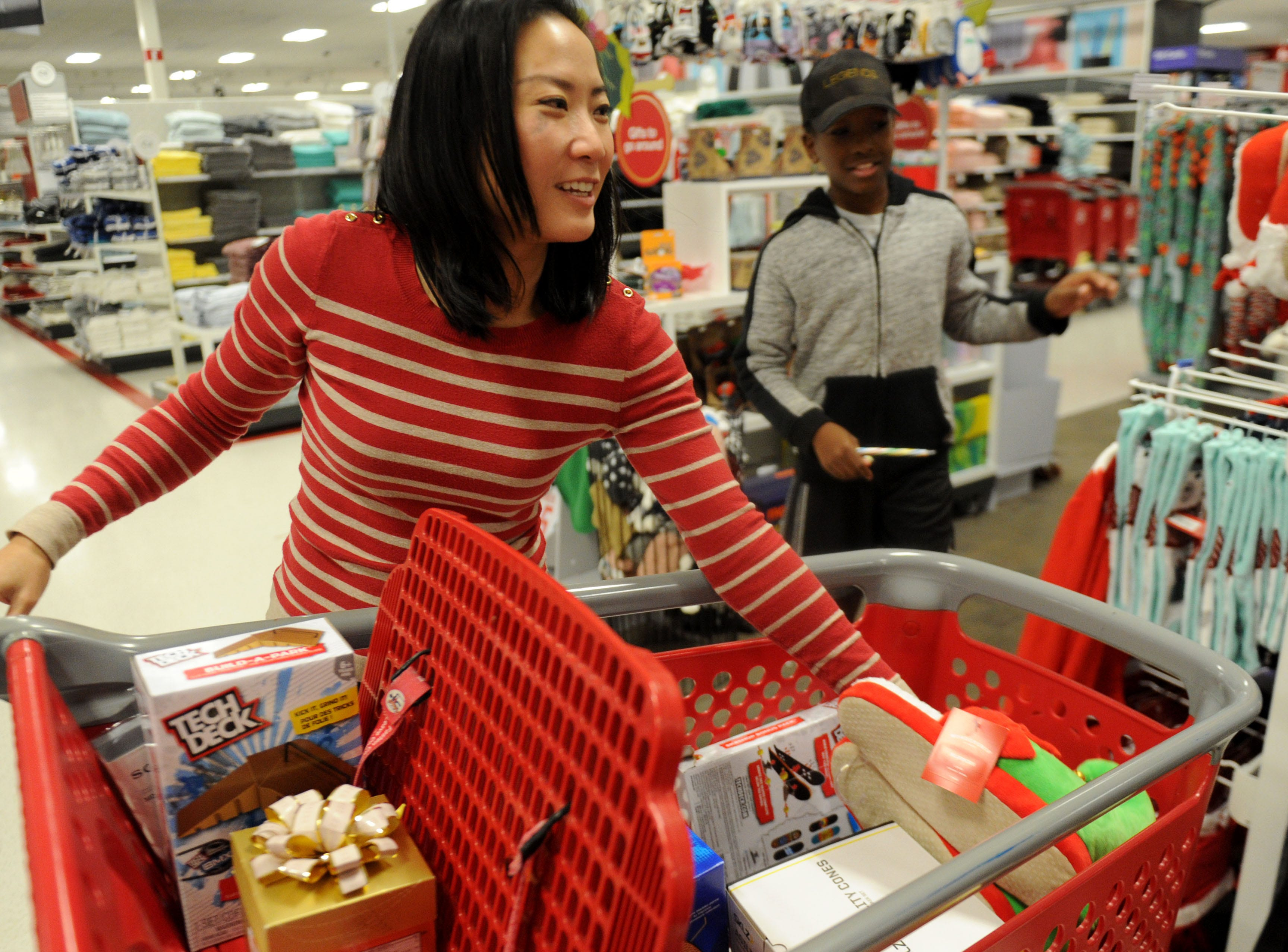 Kristina Tansavatdi of the Rotary Club of Westlake Village helps Samuel Opoku select a gift for his mom. The club hosted a shopping spree at Target for 36 members of the Boys & Girls Club. The children, each with $110 to spend, were paired with 36 volunteers, and they also got two $10 gift cards so they could buy gifts for someone else.