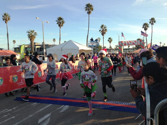 Runners start the 5K portion of the 11th annual Santa to the Sea on Sunday at the Marine Emporium Landing in Channel Islands Harbor in Oxnard. The nonprofit event helps collect toys for underprivileged children throughout Ventura County and raises scholarship money for students at Oxnard College.