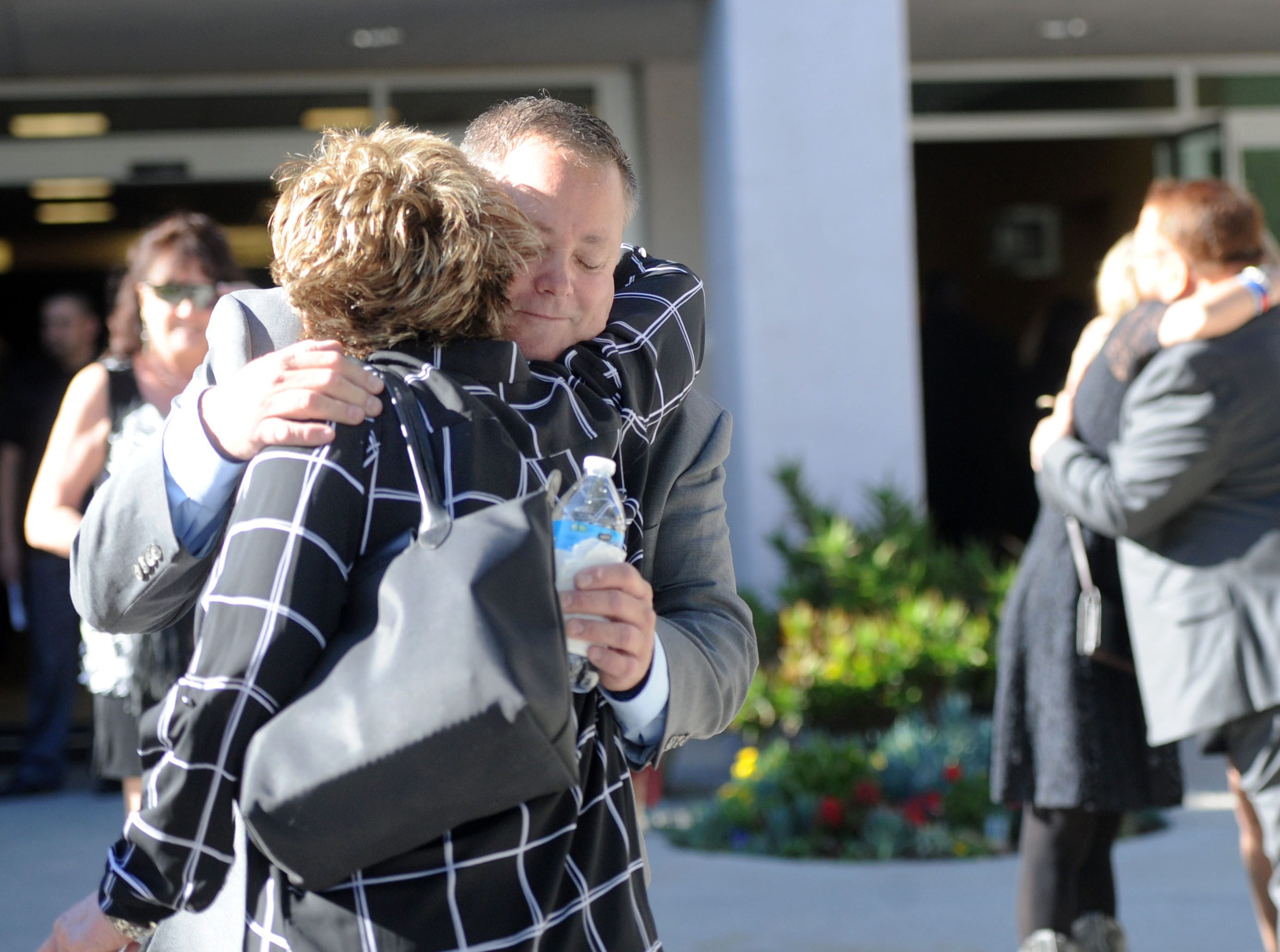 Ken Dunham gets hugs along with his wife, Kathy Dunham, in back, at the start of the memorial service for their son Jake Dunham, one of the Borderline Bar & Grill shooting victims.