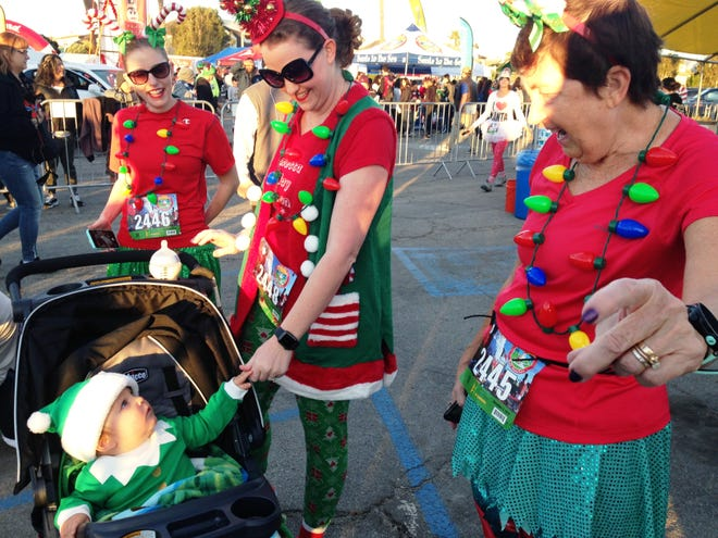 Raquel Arciniega, of Los Angeles, plays with R.J. Arciniega, 11 months, at the Santa to the Sea event Sunday at the Marine Emporium Landing at Channel Islands Harbor in Oxnard.  They are pictured with Rhea Rebbe (left) and Michelle Rebbe (right). This was the 11th year for the race, which helps collect toys for underprivileged children throughout Ventura County and raises scholarship money for students at Oxnard College.
